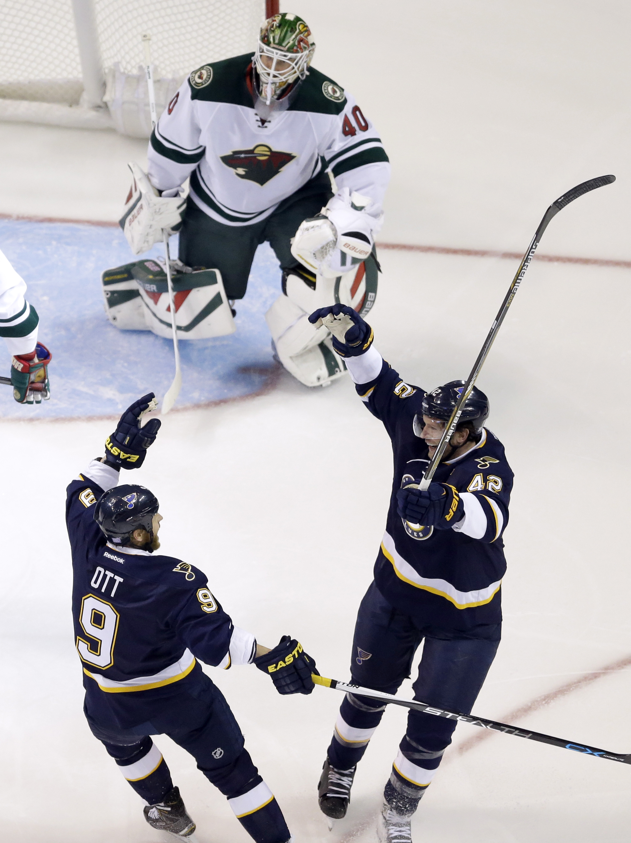 St. Louis Blues' David Backes, bottom right, is congratulated by teammate Steve Ott after scoring past Minnesota Wild goalie Devan Dubnyk, top, during the first period of an NHL hockey game Saturday, Oct. 31, 2015, in St. Louis. (AP Photo/Jeff Roberson)
