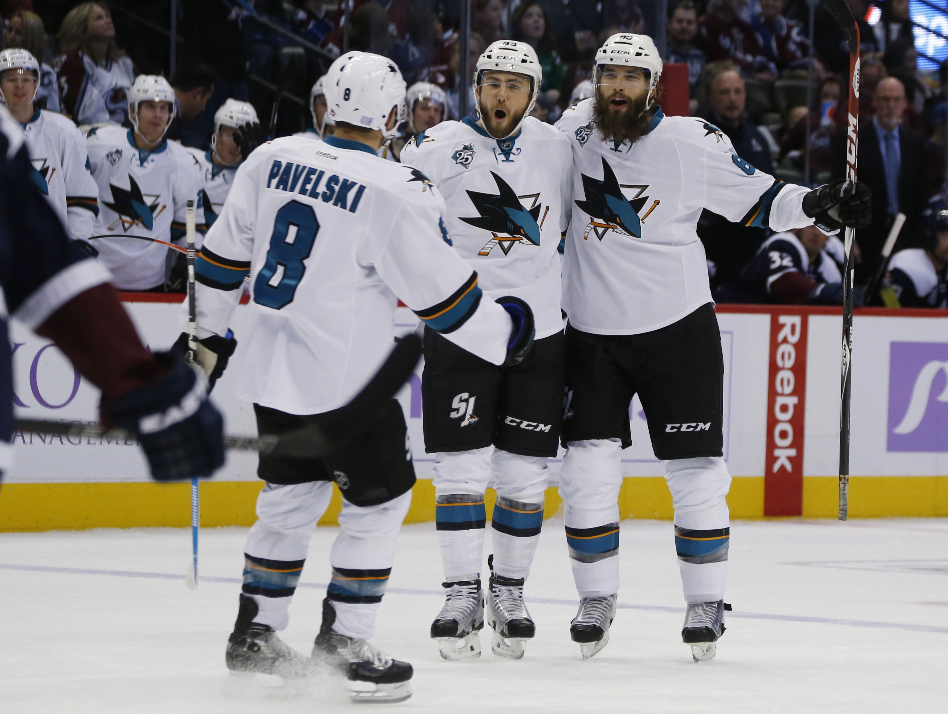 San Jose Sharks defenseman Brent Burns, right, celebrates scoring a short-handed goal against the Colorado Avalanche with teammates Marc-Edouard Vlasic, center, and Joe Pavelski in the second period of an NHL hockey game Sunday, Nov. 1, 2015, in Denver. (