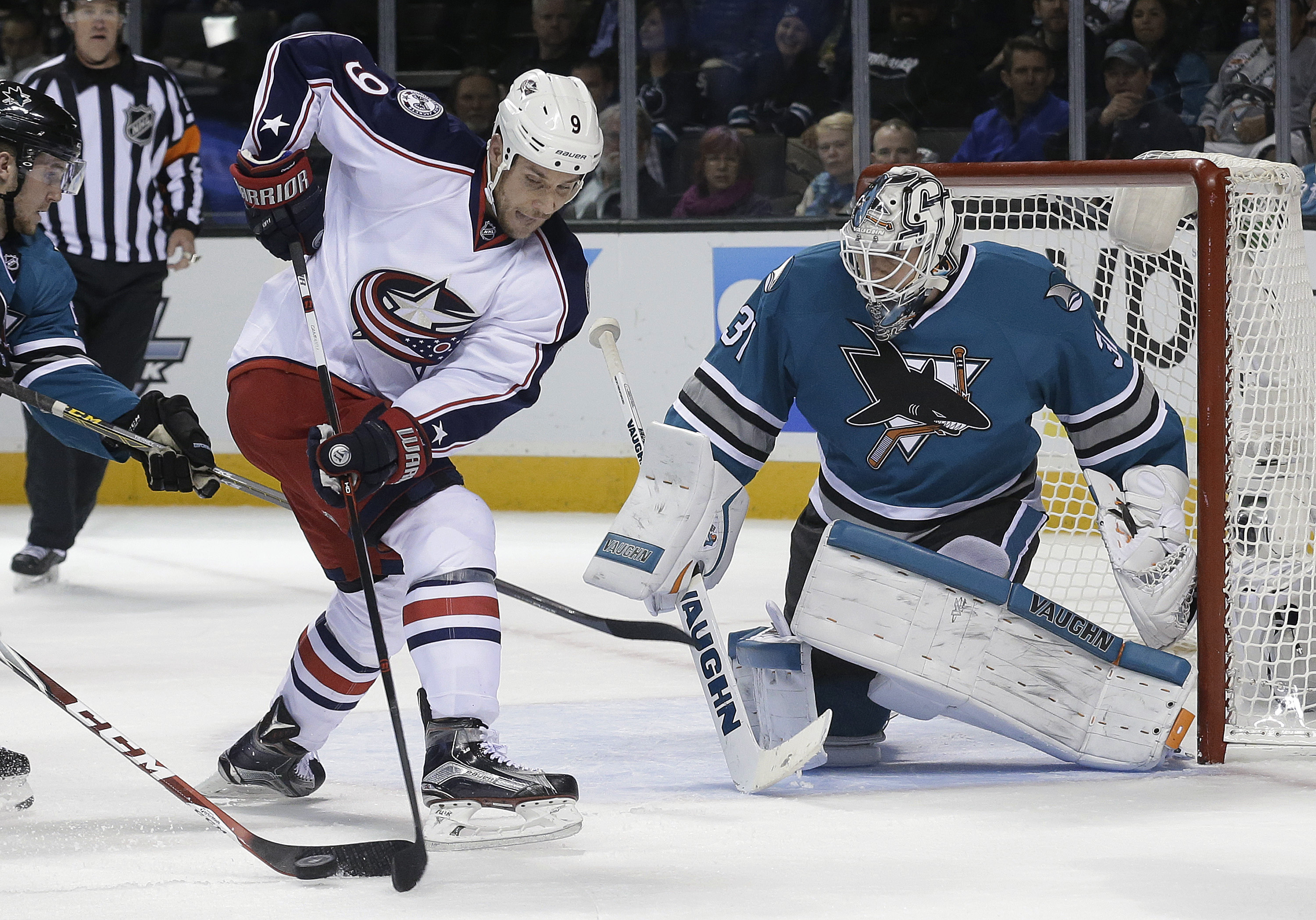 Columbus Blue Jackets center Gregory Campbell (9) reaches for the puck next to San Jose Sharks goalie Martin Jones (31) during the second period of an NHL hockey game in San Jose, Calif., Tuesday, Nov. 3, 2015. (AP Photo/Jeff Chiu)
