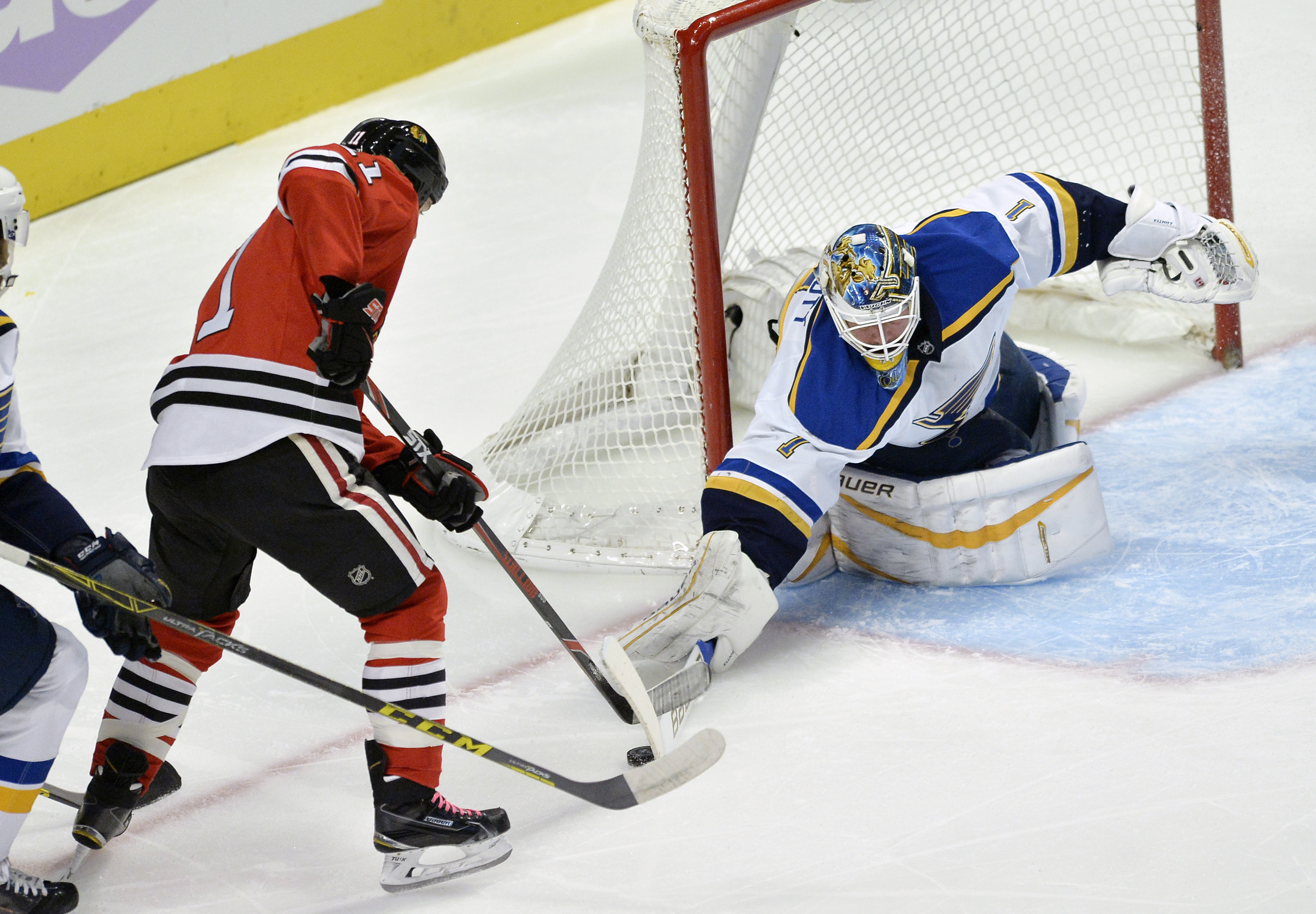 St. Louis Blues goalie Brian Elliot (1), makes a save against Chicago Blackhawks' Andrew Desjardins (11), during the first period of a hockey game Wednesday, Nov. 4, 2015, in Chicago. (AP Photo/Paul Beaty)