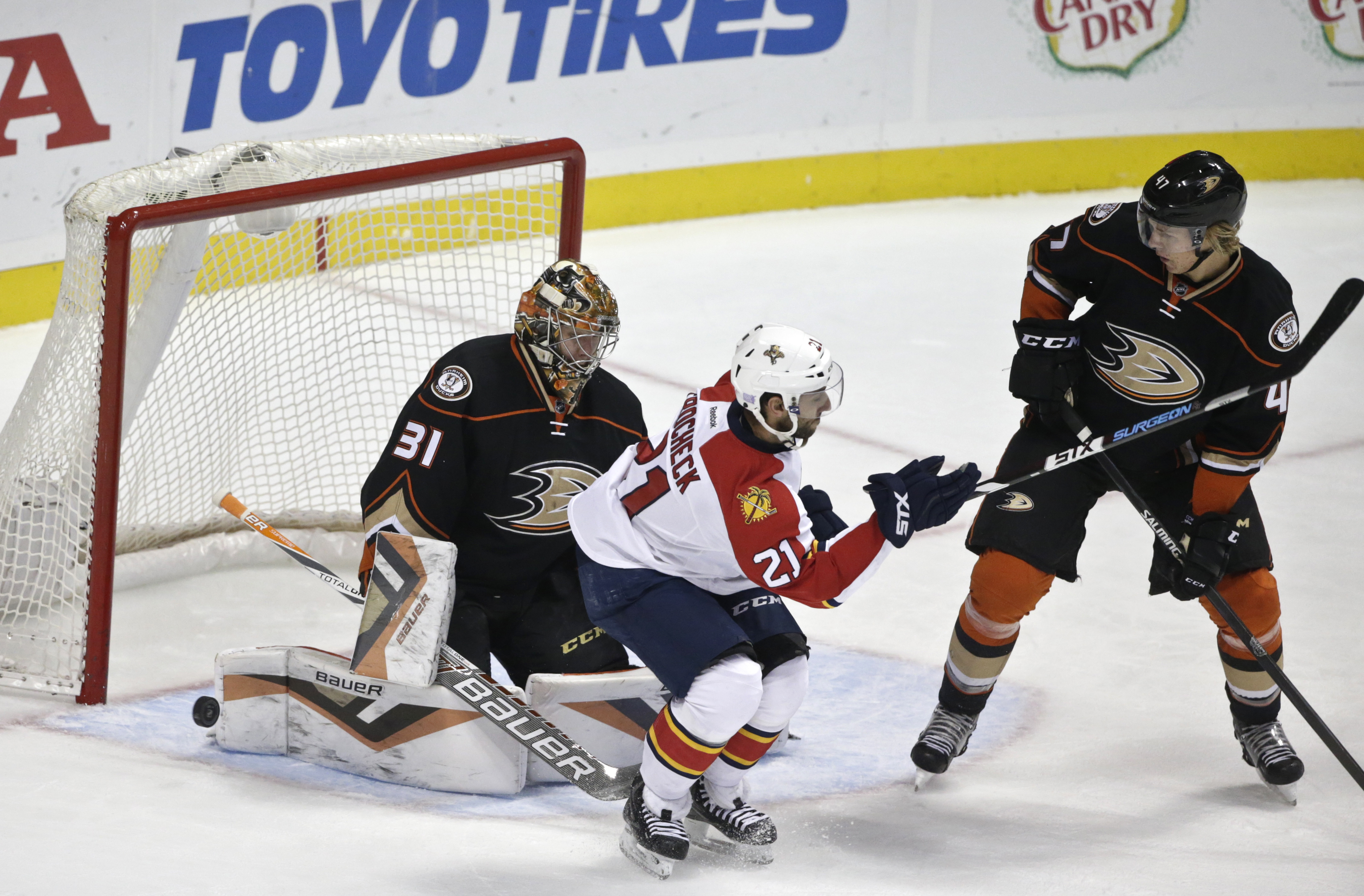 The puck slides past Anaheim Ducks goalie Frederik Andersen but misses the net while Anaheim Ducks defenseman Hampus Lindholm battles Florida Panthers center Vincent Trocheck in front of the net during the first period of an NHL hockey game  Wednesday, No