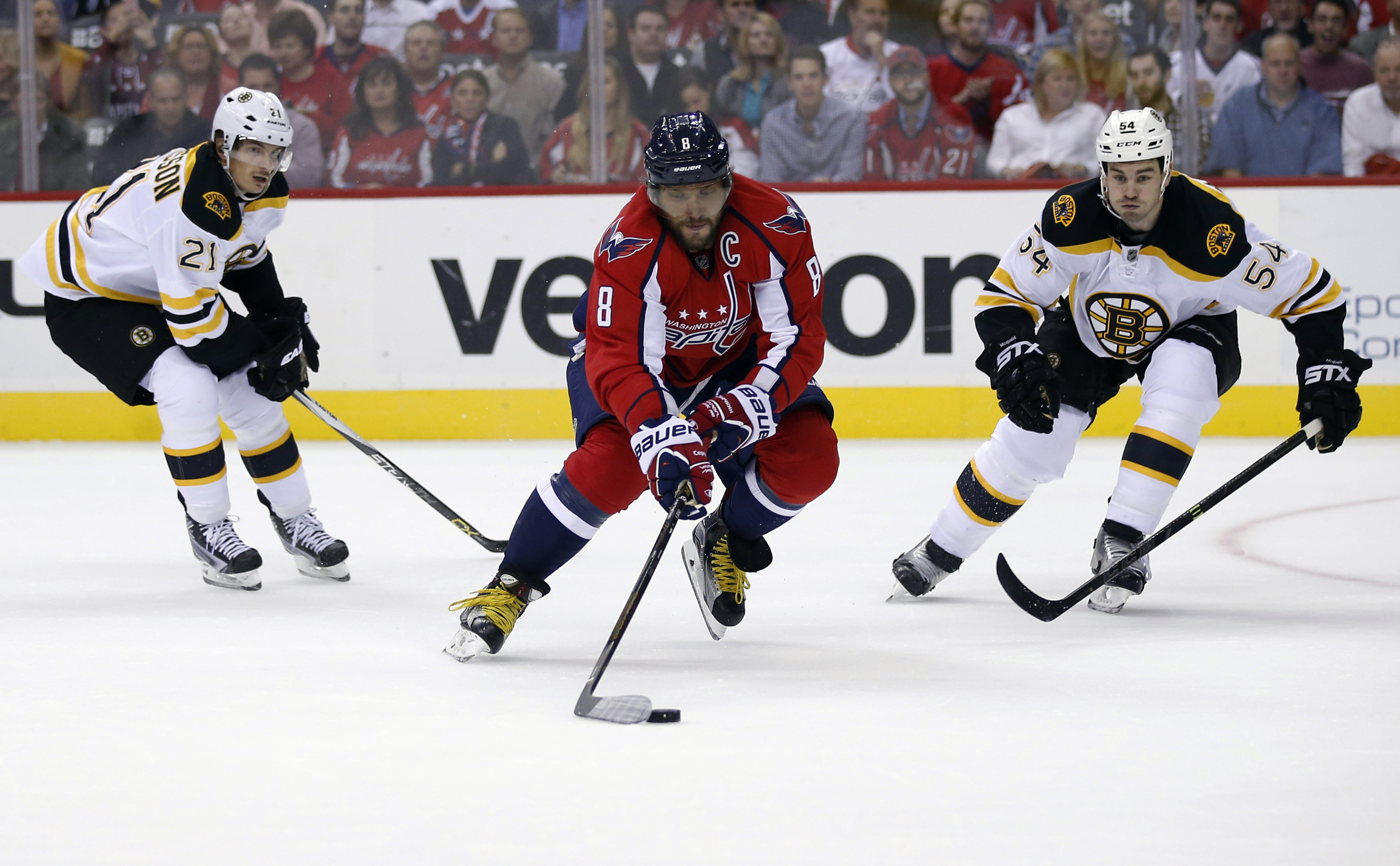 Washington Capitals left wing Alex Ovechkin (8), from Russia, skates with the puck between Boston Bruins left wing Loui Eriksson (21), from Sweden, and defenseman Adam McQuaid (54) during the first period of an NHL hockey game, Thursday, Nov. 5, 2015, in