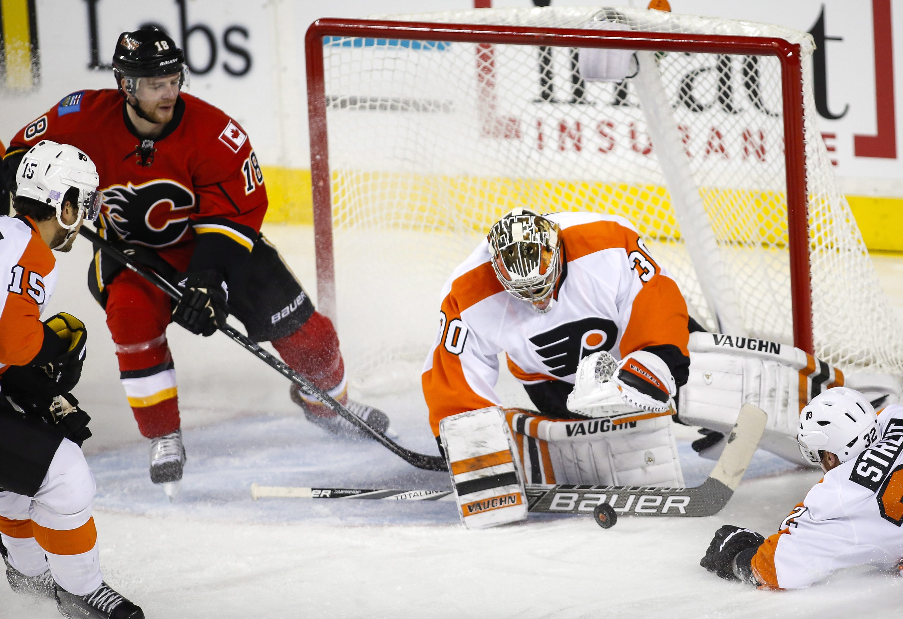 Philadelphia Flyers' goalie Michal Neuvirth (30), of the Czech Republic, grabs for the puck as Calgary Flames' Matt Stajan (18) looks on during second-period NHL hockey game action in Calgary, Alberta, Thursday, Nov. 5, 2015. (Jeff McIntosh/The Canadian P