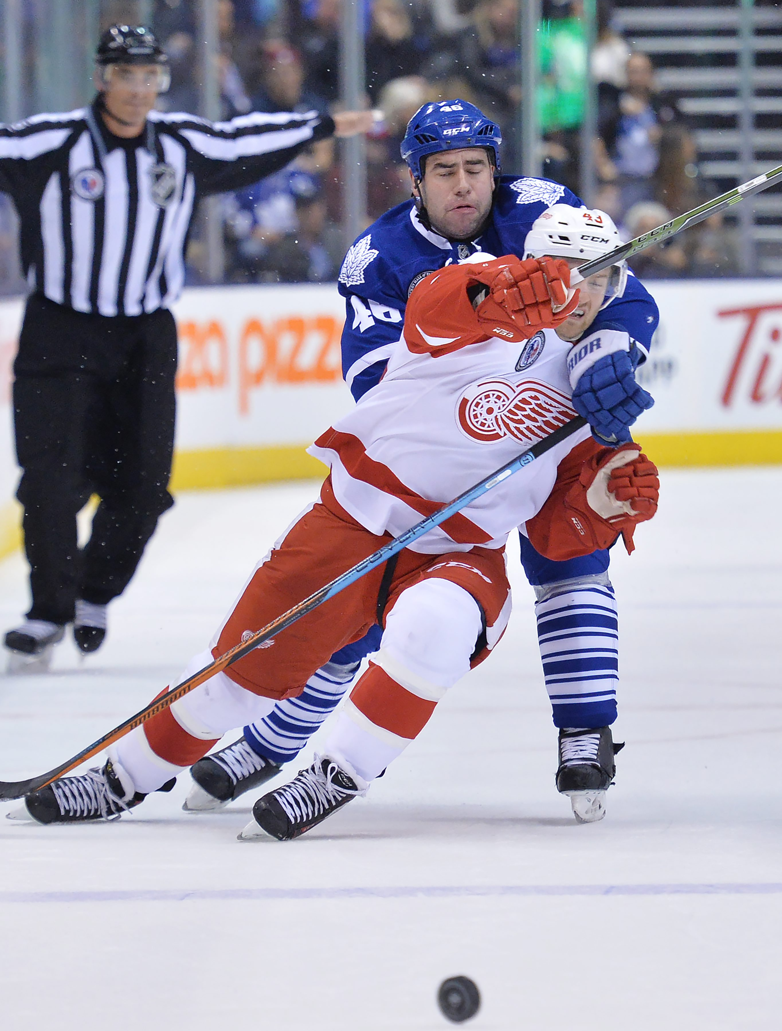 Toronto Maple Leafs' defender Roman Polack (46) trips Detroit Red Wings forward Darren Helm (43) during first-period NHL hockey game action in Toronto, Friday, Nov. 6, 2015. (Nathan Denette/The Canadian Press via AP) MANDATORY CREDIT