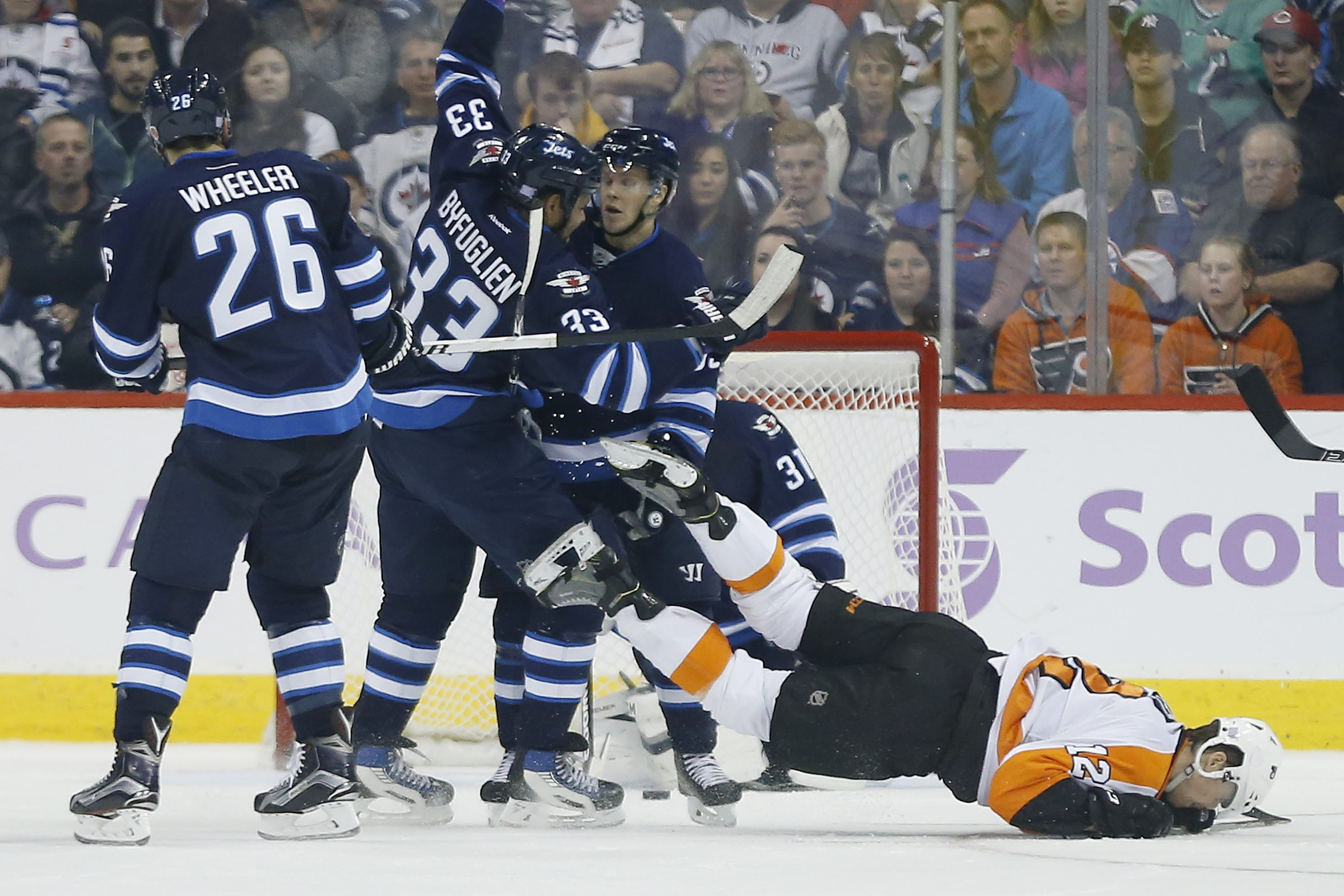Philadelphia Flyers' Michael Raffl (12) hits the ice hard after he gets dumped by Winnipeg Jets' Dustin Byfuglien (33) during second period NHL action, in Winnipeg, on Saturday, Nov. 7, 2015. (John Woods/The Canadian Press via AP)