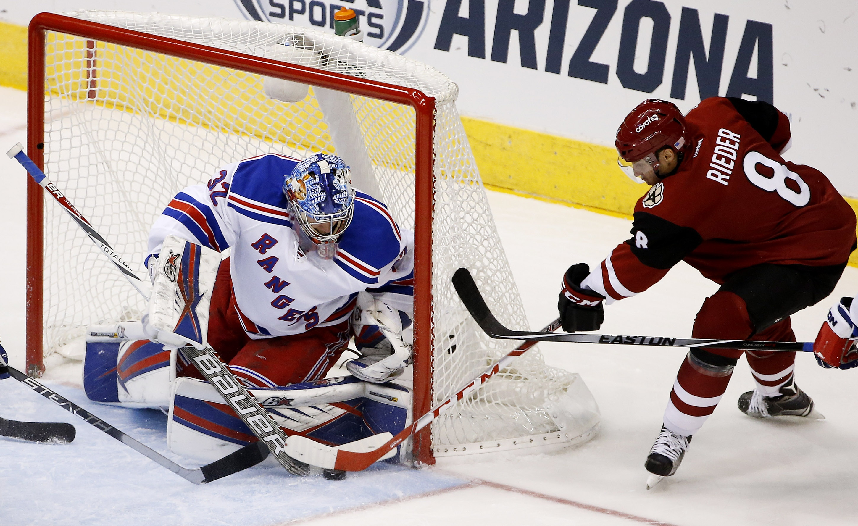 New York Rangers' Antti Raanta (32), of Finland, makes a save on a shot by Arizona Coyotes' Tobias Rieder (8), of Germany, during the first period of an NHL hockey game Saturday, Nov. 7, 2015, in Glendale, Ariz. (AP Photo/Ross D. Franklin)