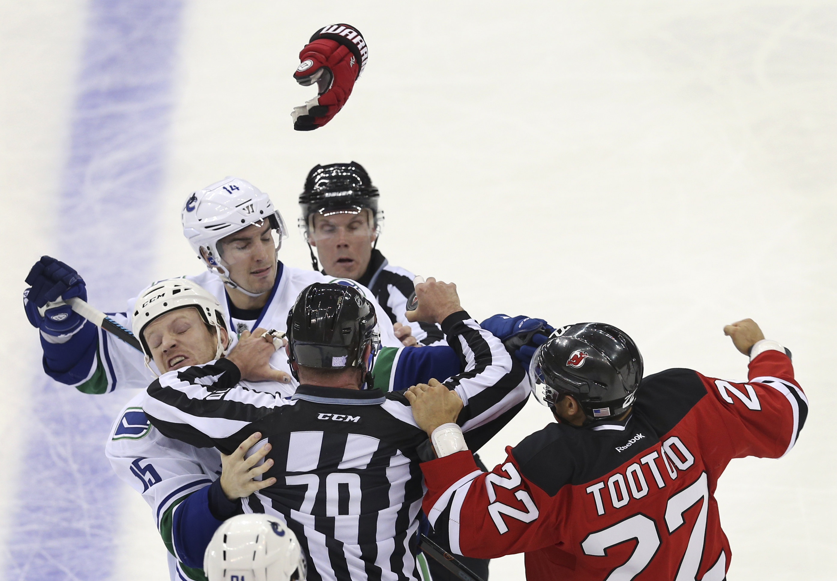 New Jersey Devils right wing Jordin Tootoo (22) fights with Vancouver Canucks right wingers Alexandre Burrows (14) and Derek Dorsett (15) during the second period of an NHL hockey game, Sunday, Nov. 8, 2015, Newark, N.J. The Devils won in overtime 4-3. (A