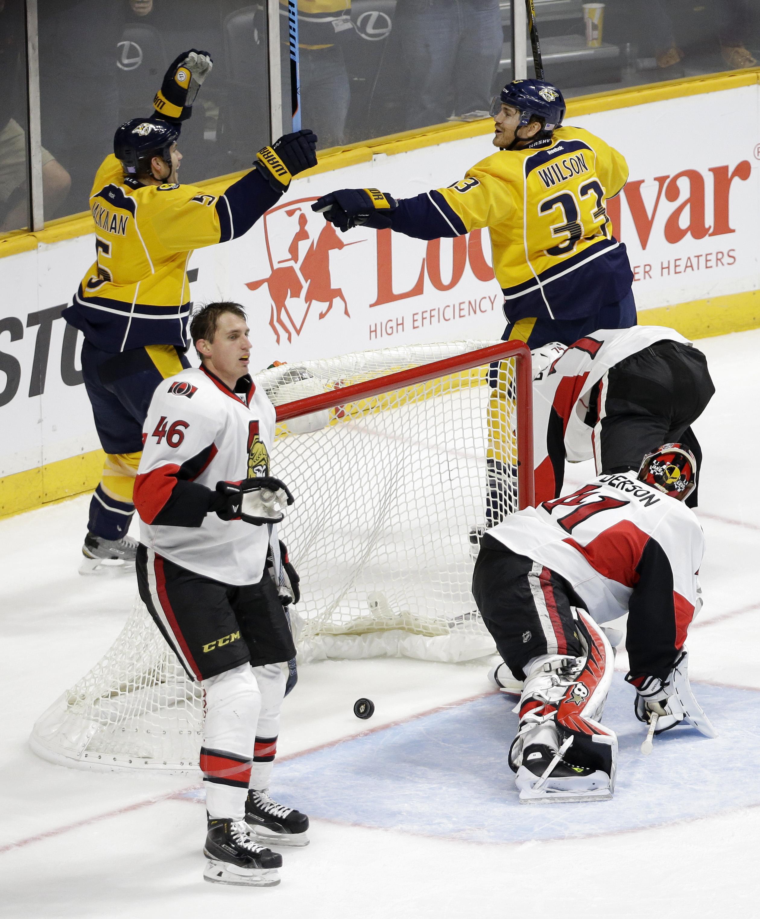 Nashville Predators defenseman Barret Jackman (5) celebrates with Colin Wilson (33) after Jackman scored against Ottawa Senators goalie Craig Anderson (41) during the third period of an NHL hockey game Tuesday, Nov. 10, 2015, in Nashville, Tenn.  At front
