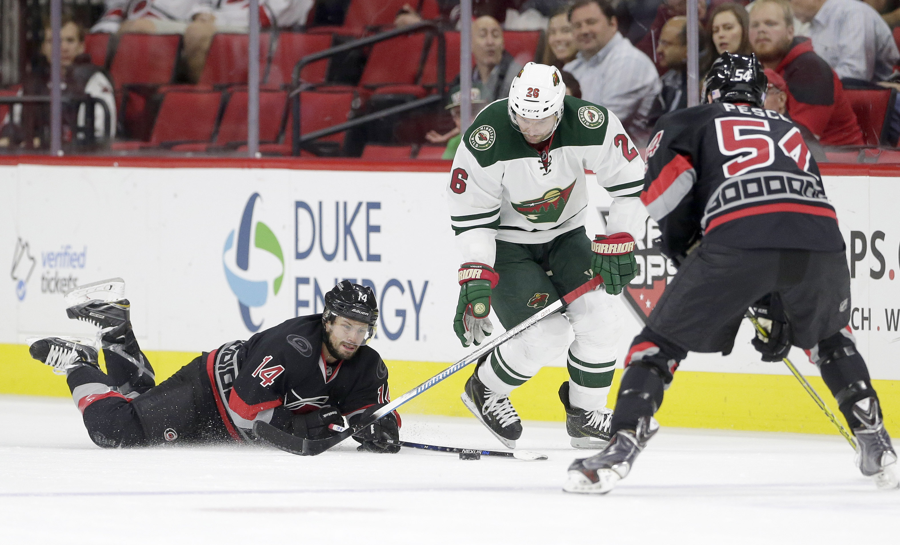 Carolina Hurricanes' Nathan Gerbe (14) and Brett Pesce (54) struggle for possession of the puck with Minnesota Wild's Thomas Vanek (26), of Austria, during the first period of an NHL hockey game in Raleigh, N.C., Thursday, Nov. 12, 2015. (AP Photo/Gerry B