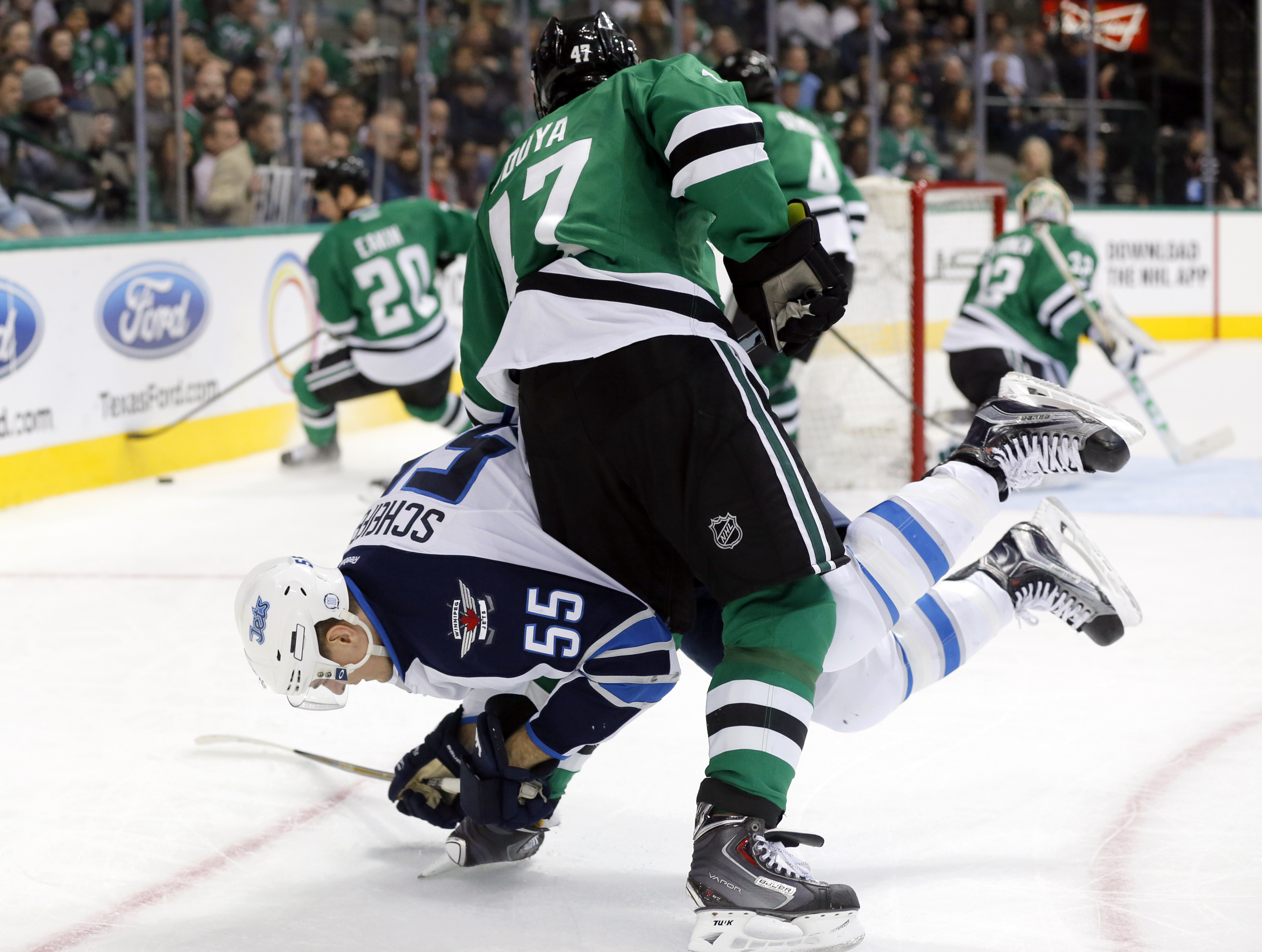 Winnipeg Jets' Mark Scheifele (55) and Dallas Stars' Johnny Oduya, of Sweden, become entangled in the corner in the second period of an NHL hockey game Thursday, Nov. 12, 2015, in Dallas. (AP Photo/Tony Gutierrez)
