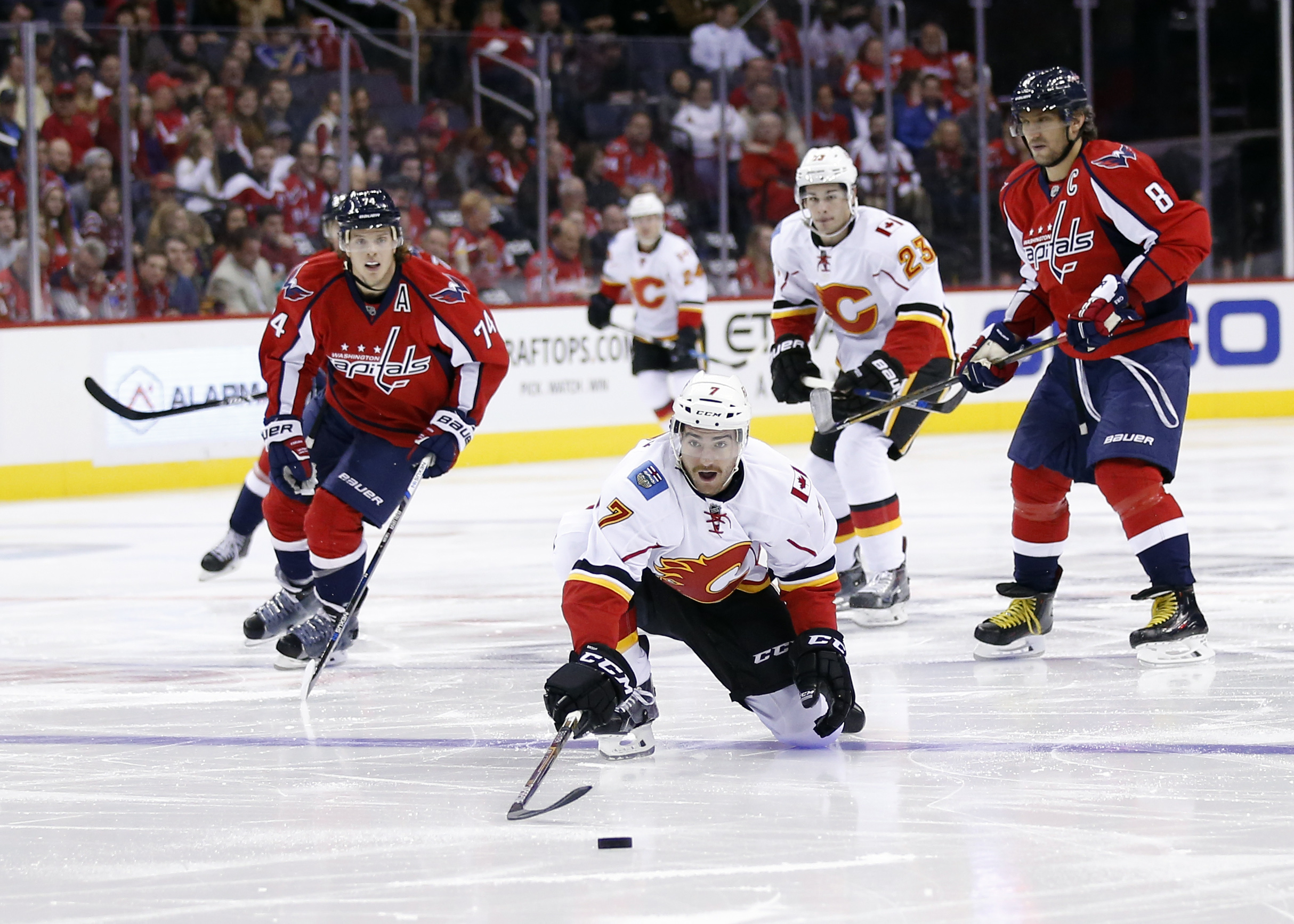 Calgary Flames defenseman T.J. Brodie (7) lunges for the puck with Washington Capitals defenseman John Carlson (74) and left wing Alex Ovechkin (8), from Russia, nearby in the second period of an NHL hockey game, Friday, Nov. 13, 2015, in Washington. (AP