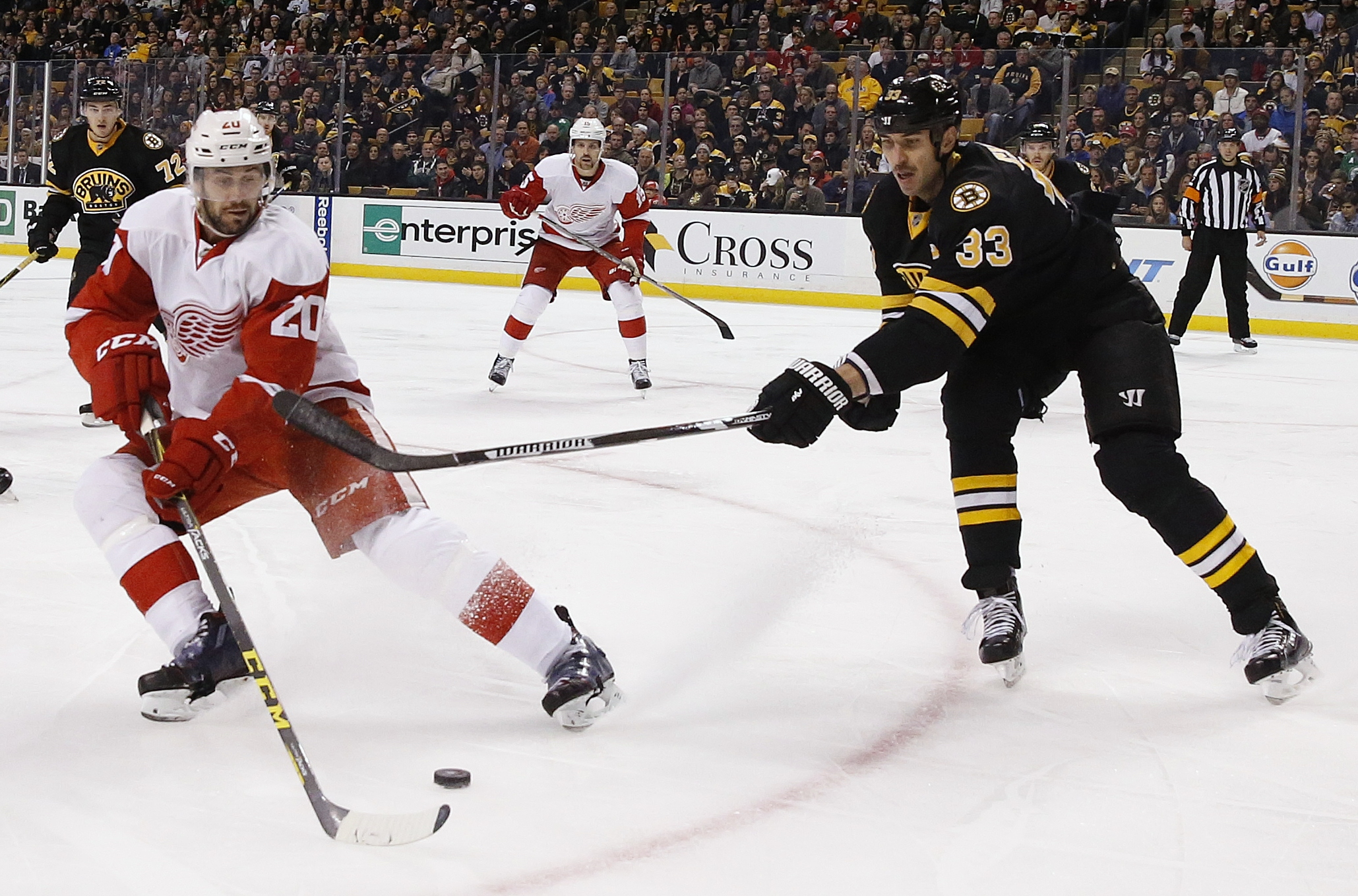 Boston Bruins' Zdeno Chara (33) battles Detroit Red Wings' Drew Miller (20) for the puck during the first period of an NHL hockey game in Boston, Saturday, Nov. 14, 2015. (AP Photo/Michael Dwyer)