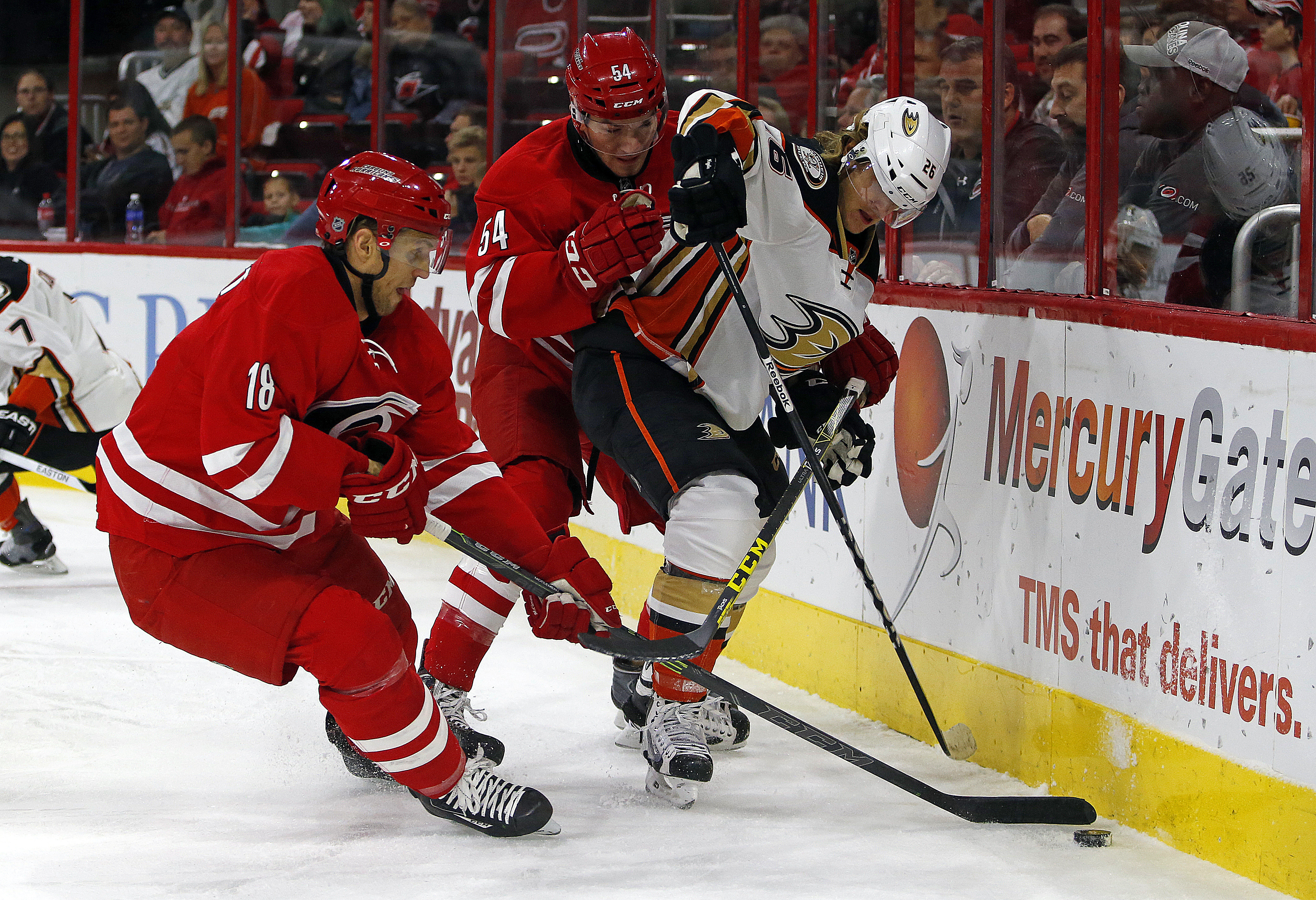 Carolina Hurricanes' Jay McClement (18) reaches for the puck as teammate Brett Pesce (54) ties up Anaheim Ducks' Carl Hagelin (26) during the first period of an NHL hockey game, Monday, Nov. 16, 2015, in Raleigh, N.C. (AP Photo/Karl B DeBlaker)