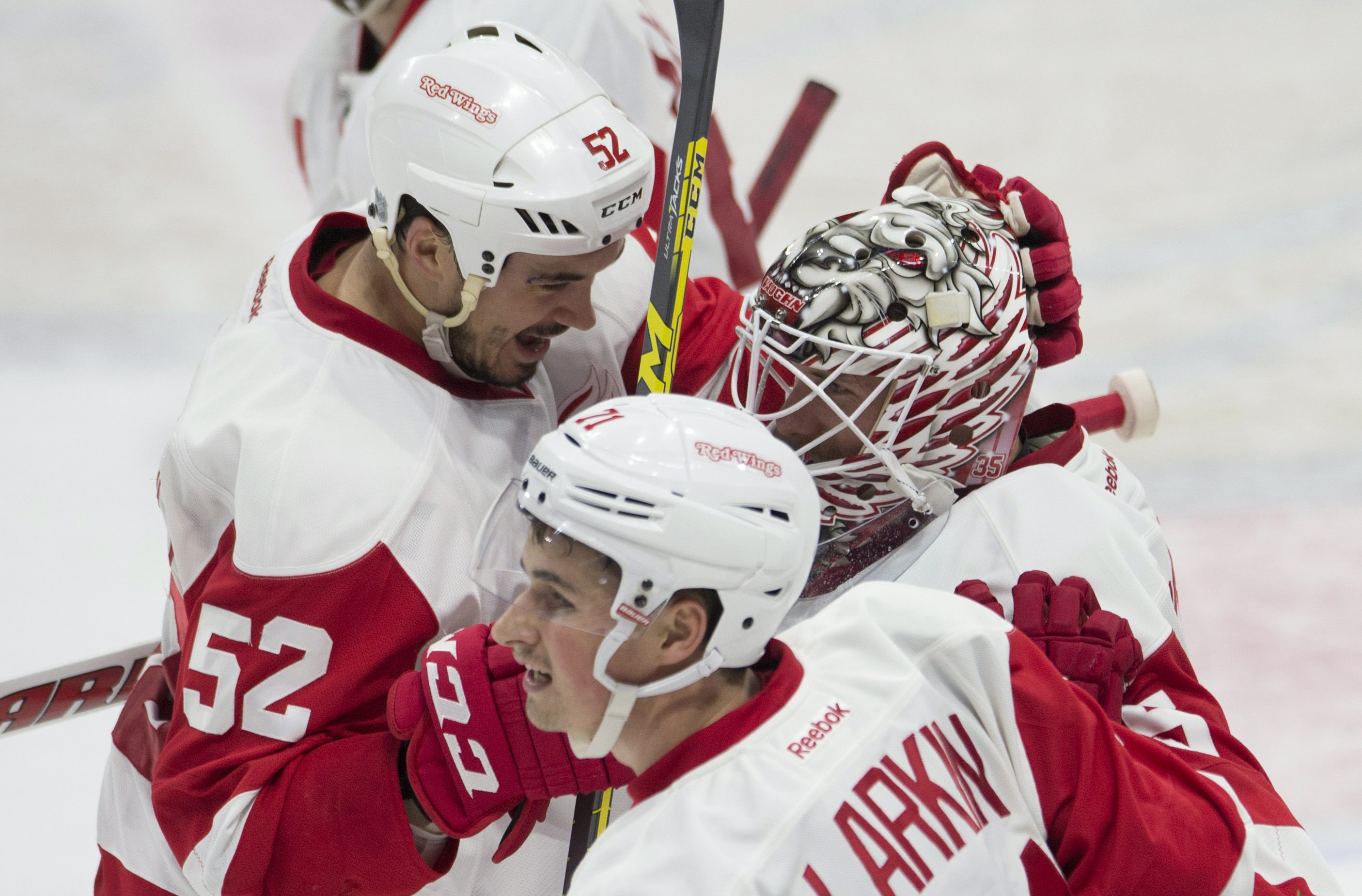 Detroit Red Wings center Dylan Larkin and defenseman Jonathan Ericsson, left, congratulate goalie Jimmy Howard after defeating the Ottawa Senators in overtime during NHL action in Ottawa, Ontario, Monday, Nov. 16, 2015. (Adrian Wyld/The Canadian Press via