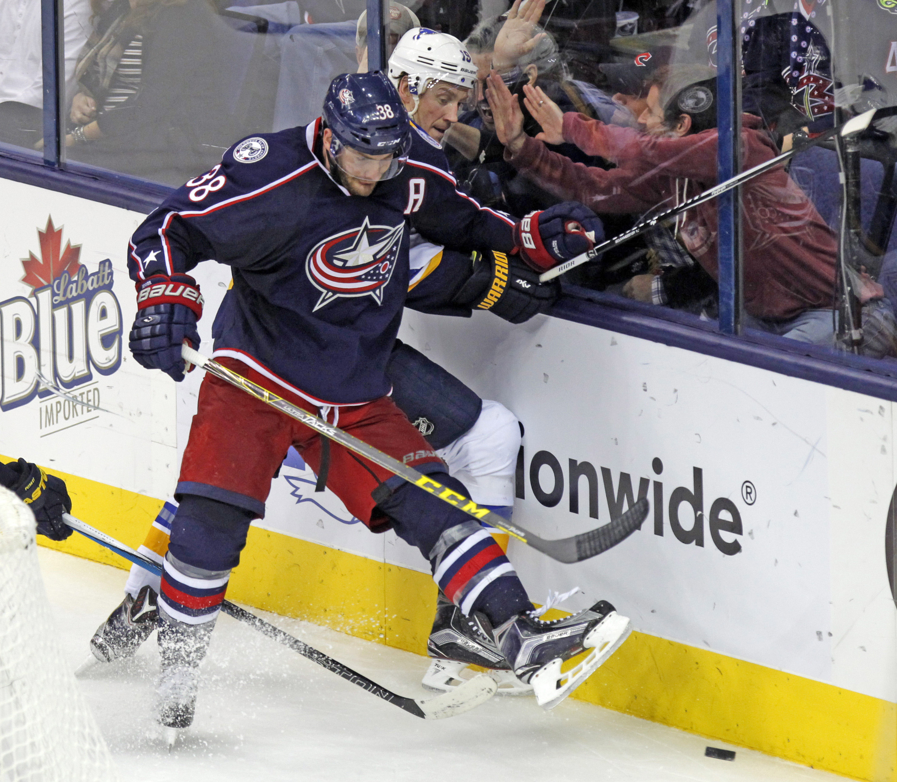 Columbus Blue Jackets' Boone Jenner, left, works for the puck against St. Louis Blues' Jay Bouwmeester during the third period of an NHL hockey game in Columbus, Ohio, Tuesday, Nov. 17, 2015. The Blue Jackets won 3-1. (AP Photo/Paul Vernon)