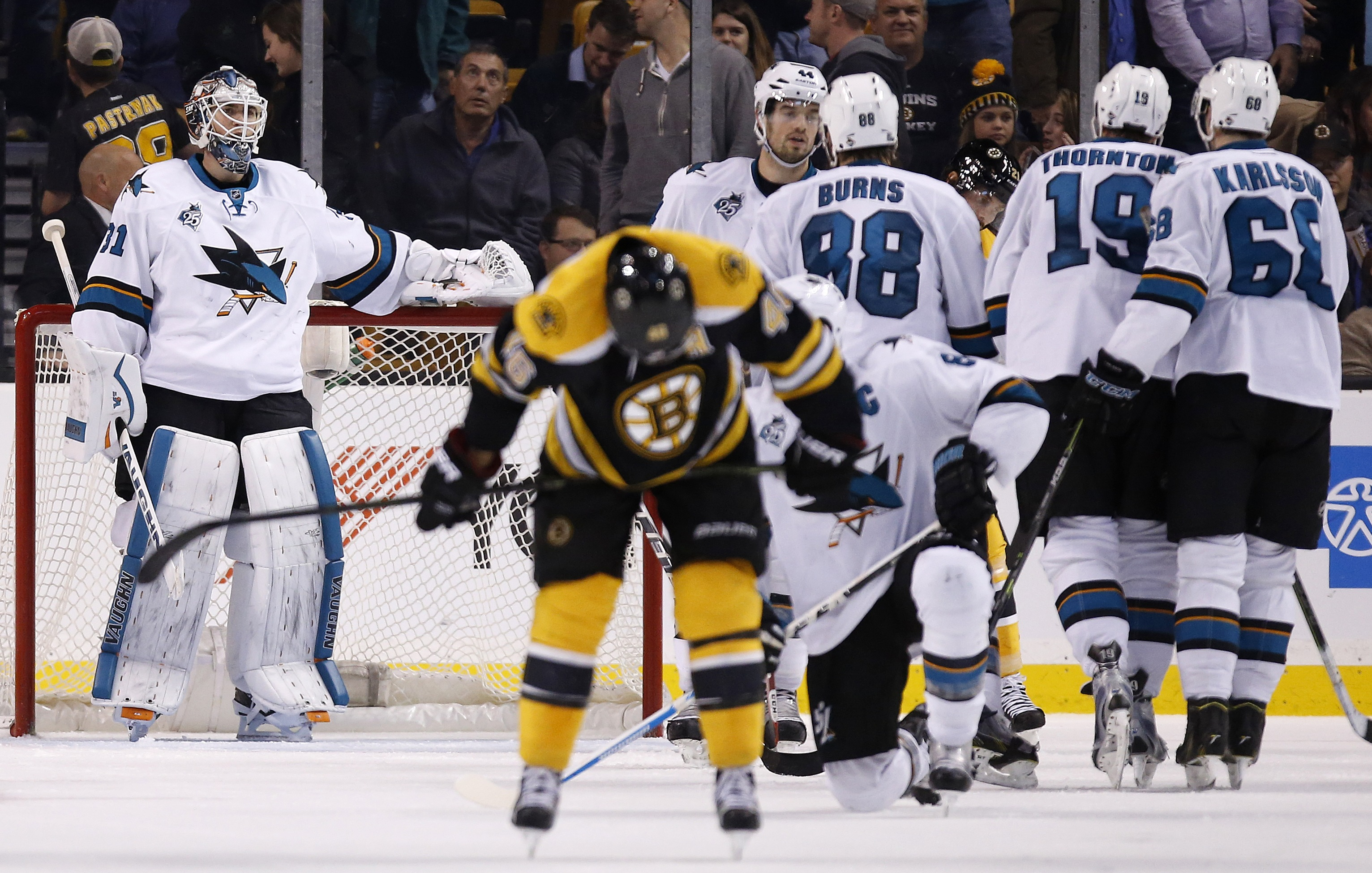 San Jose Sharks' Martin Jones, left, stands in the net and Boston Bruins' David Krejci, foreground center, skates away as the Sharks celebrate after defeating the Bruins 5-4 in an NHL hockey game in Boston, Tuesday, Nov. 17, 2015. (Photo/Michael Dwyer)