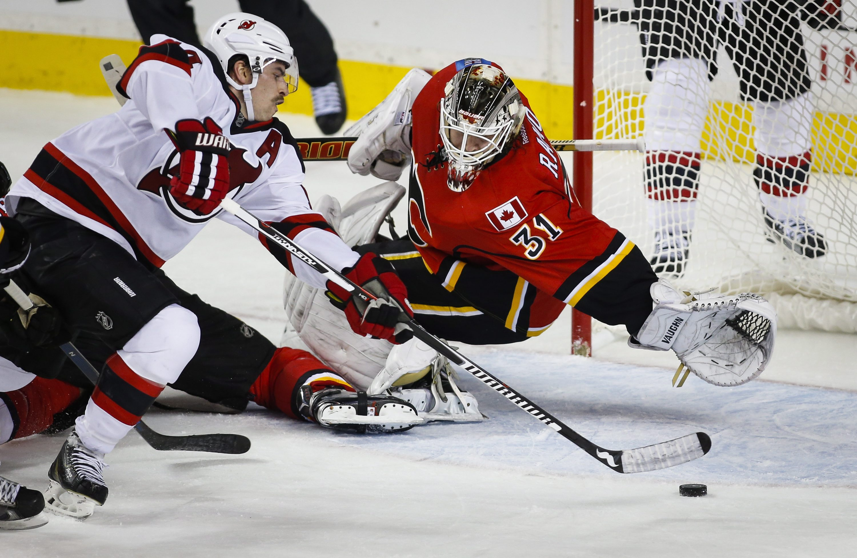 New Jersey Devils' Adam Henrique, left, dives for the puck as Calgary Flames goalie Karri Ramo, from Finland, does the same during third period NHL hockey action in Calgary, Alberta, on Tuesday, Nov. 17, 2015. (Jeff McIntosh/The Canadian Press via AP)