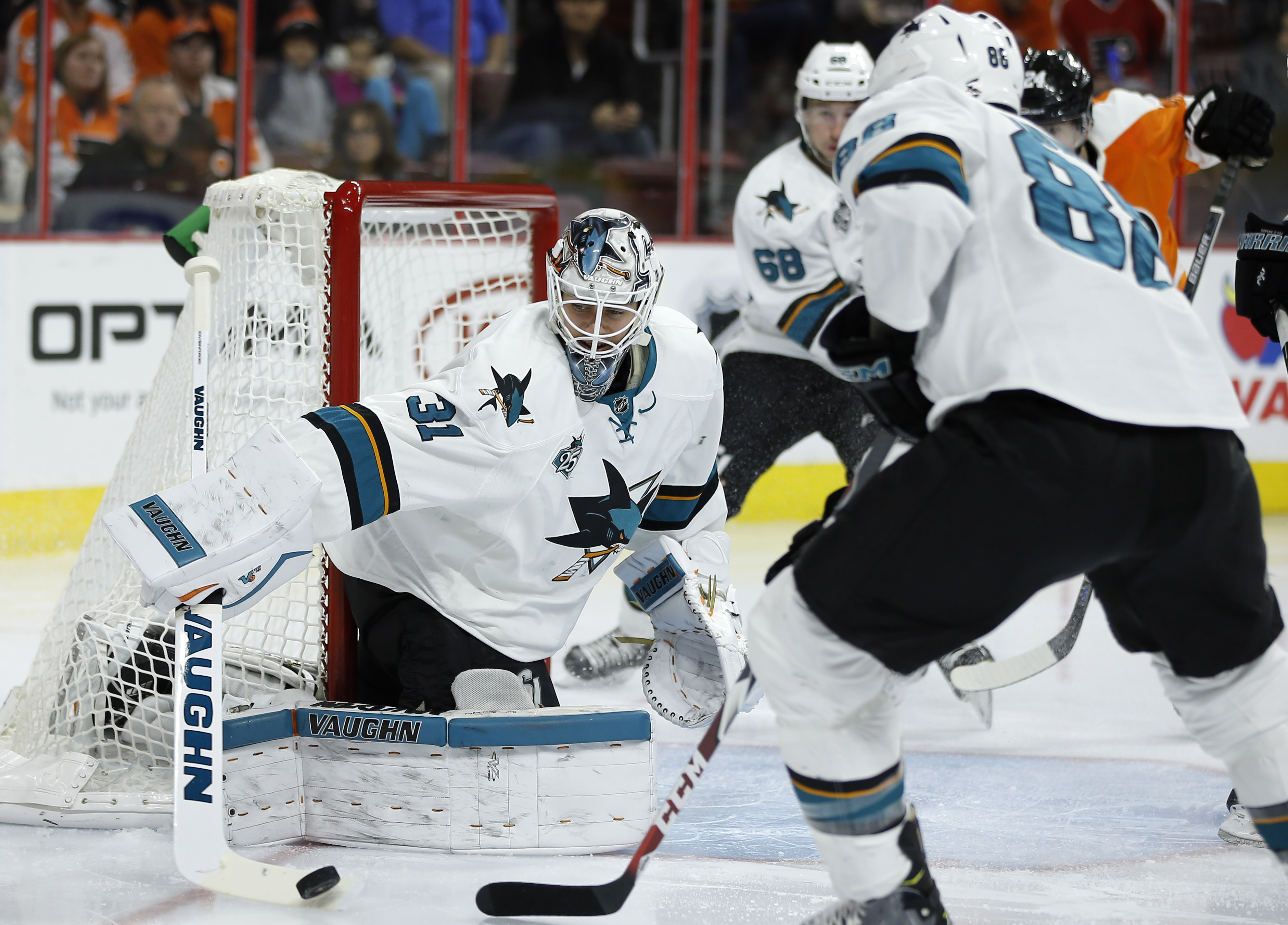 San Jose Sharks' Martin Jones, left, clears the puck as Brent Burns watches during the second period of an NHL hockey game against the Philadelphia Flyers, Thursday, Nov. 19, 2015, in Philadelphia. San Jose won 1-0 in overtime. (AP Photo/Matt Slocum)
