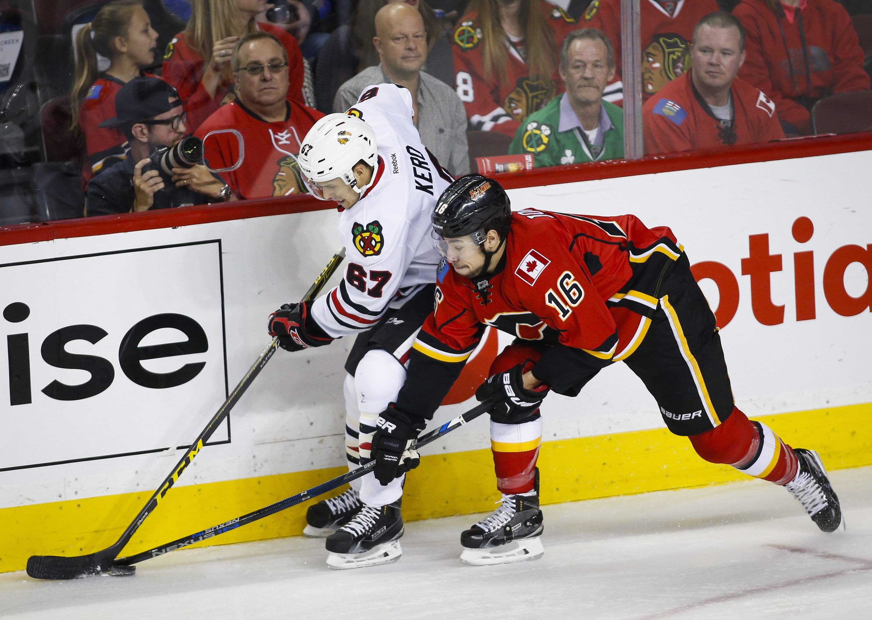 Chicago Blackhawks' Tanner Kero, left, chases the puck with Calgary Flames' Josh Jooris during the first period of an NHL hockey game Friday, Nov. 20, 2015, in Calgary, Alberta. (Jeff McIntosh/The Canadian Press via AP)