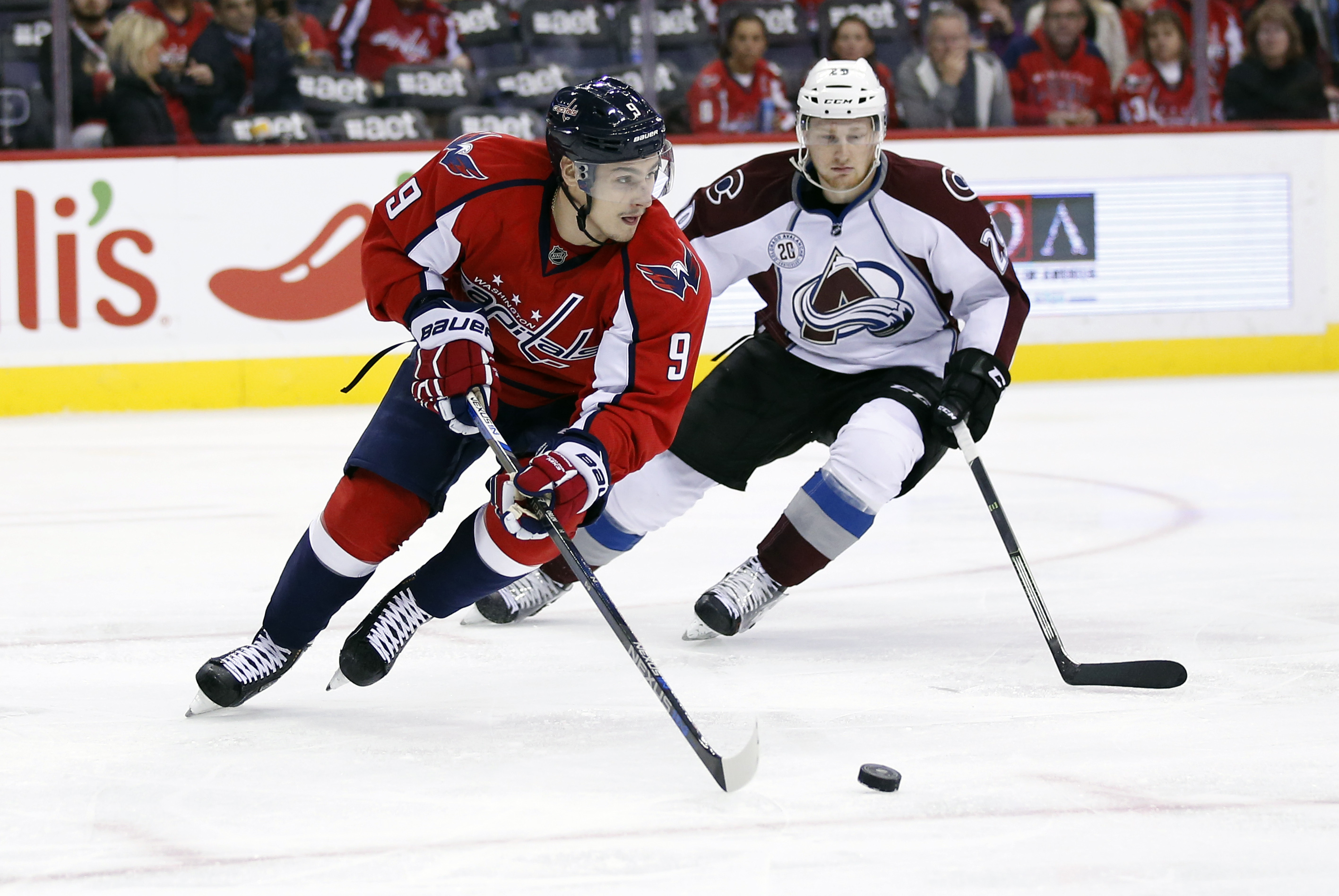 Washington Capitals defenseman Dmitry Orlov (9), from Russia, skates with the puck as Colorado Avalanche center Nathan MacKinnon (29) defends in the second period of an NHL hockey game, Saturday, Nov. 21, 2015, in Washington. (AP Photo/Alex Brandon)