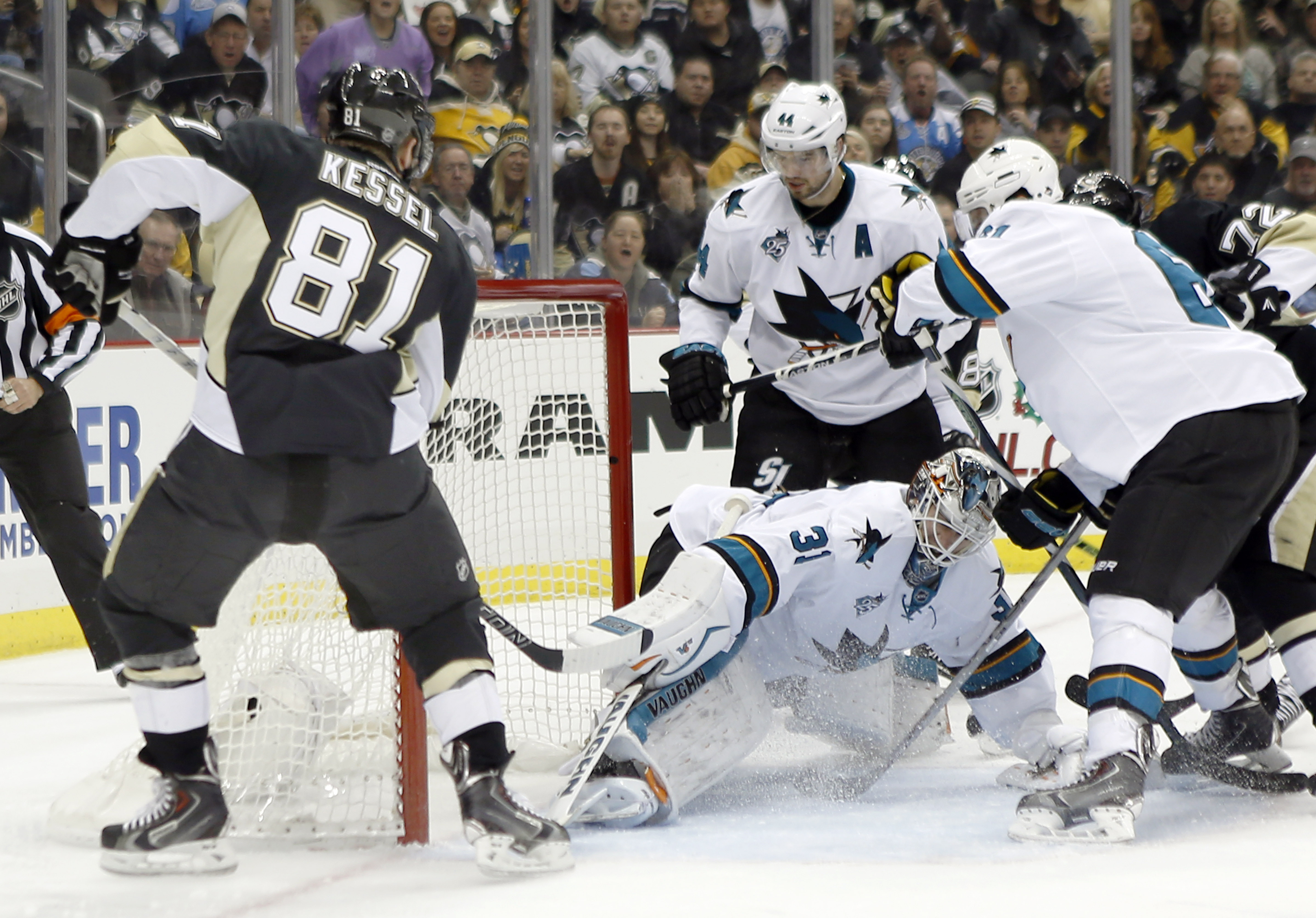 Pittsburgh Penguins' Phil Kessel (81) scores a goal over San Jose Sharks goalie Martin Jones (31) as Marc-Edouard Vlasic (44) and Justin Braun, right, defend in the second period of an NHL hockey game, Saturday, Nov. 21, 2015, in Pittsburgh. (AP Photo/Kei