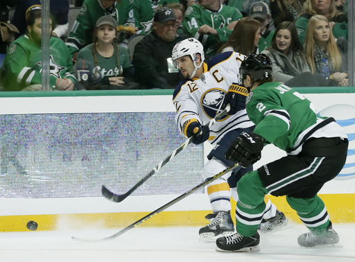 Buffalo Sabres right wing Brian Gionta (12) takes a shot at the net as Dallas Stars' Jyrki Jokipakka (2) of Finland defends in the second period of an NHL hockey game, Saturday, Nov. 21, 2015, in Dallas. (AP Photo/Tony Gutierrez)