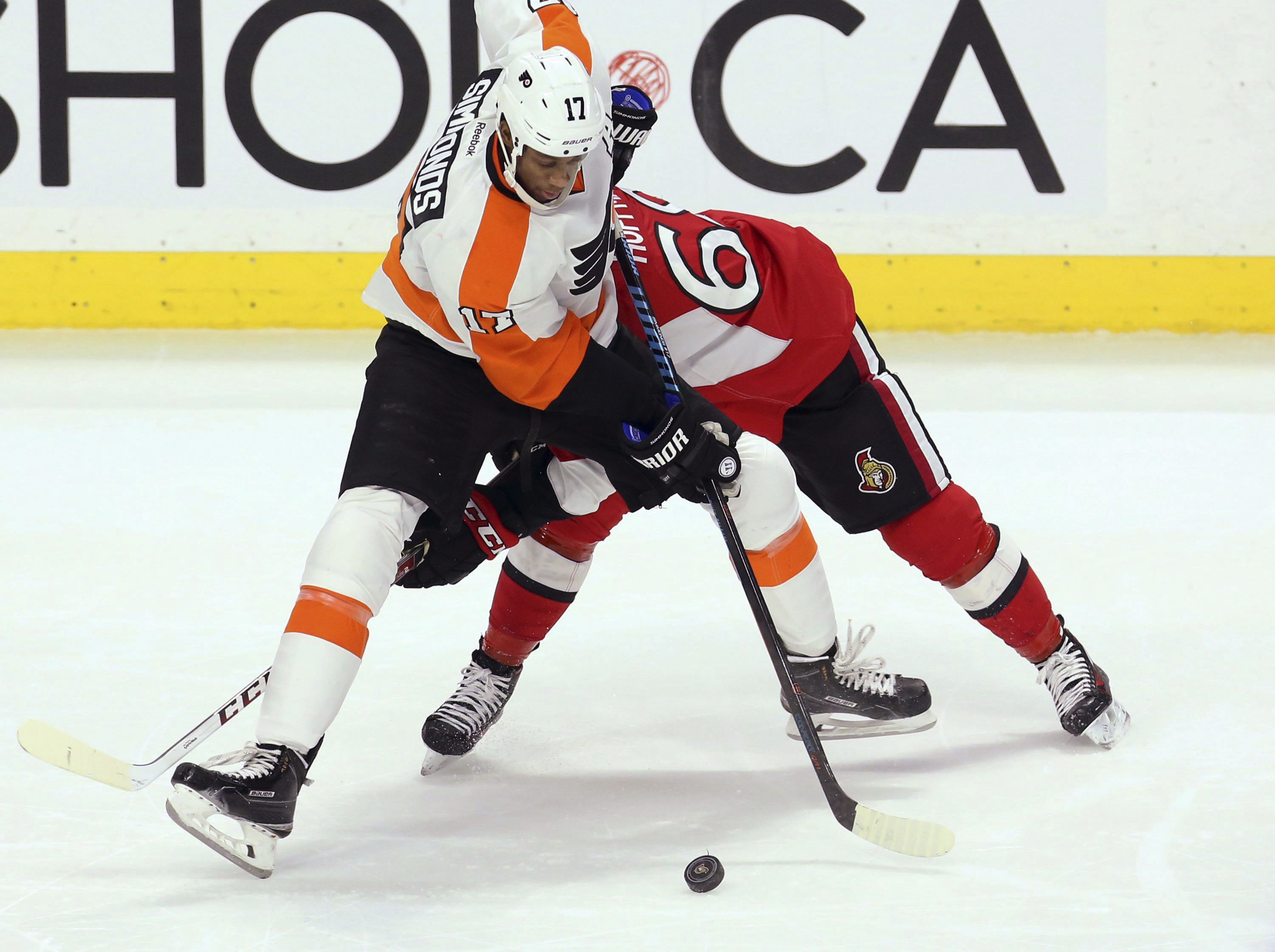 Philadelphia Flyers' Wayne Simmonds (17) fights for the puck with Ottawa Senators' Mike Hoffman (68) during the second period of an NHL hockey game Saturday, Nov. 21, 2015, in Ottawa, Ontario. (Fred Chartrand/The Canadian Press via AP)