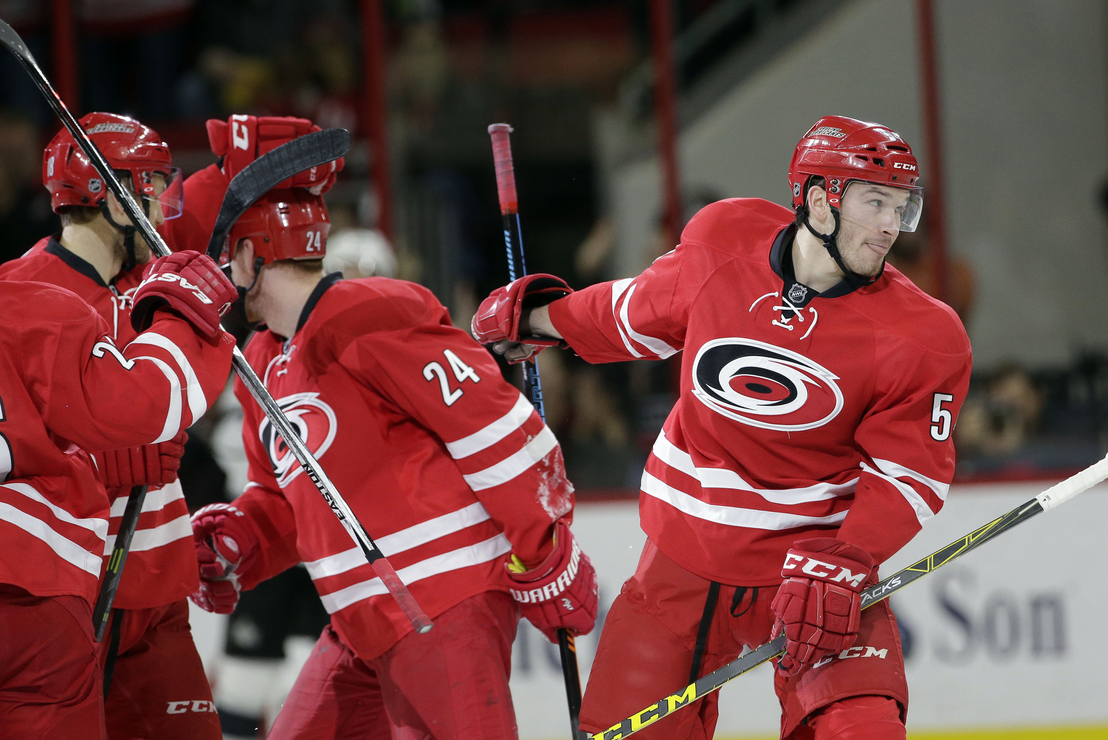 Carolina Hurricanes' Brett Pesce, right, celebrates with teammates Brad Malone (24) and Jay McClement, left, following his goal against the Los Angeles Kings during the first period of an NHL hockey game in Raleigh, N.C., Sunday, Nov. 22, 2015. (AP Photo/