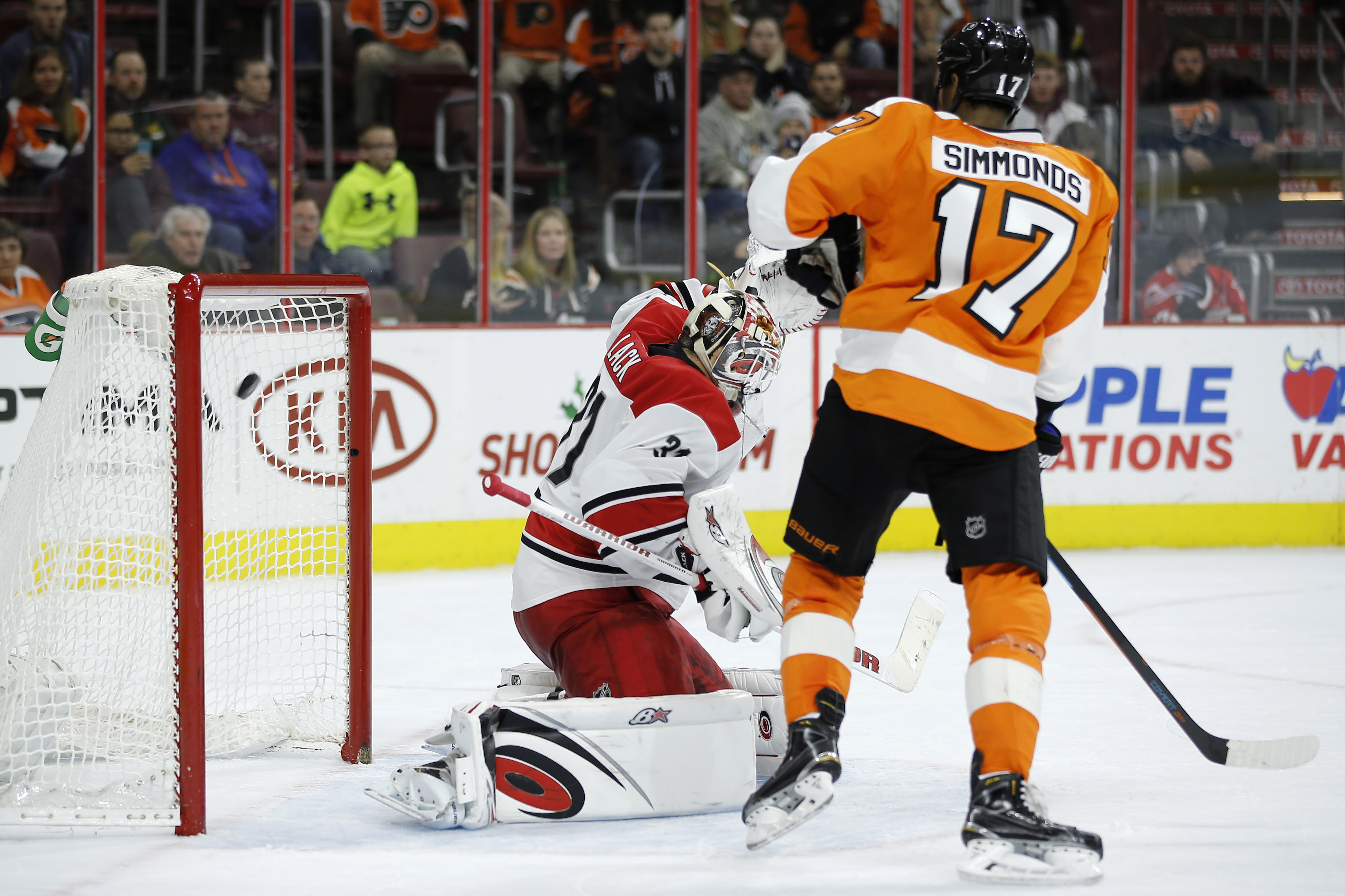 Carolina Hurricanes' Eddie Lack, left, cannot stop the game-winning goal by Philadelphia Flyers' Shayne Gostisbehereas as Wayne Simmonds (17) looks on during overtime of an NHL hockey game against the Carolina Hurricanes, Monday, Nov. 23, 2015, in Philade
