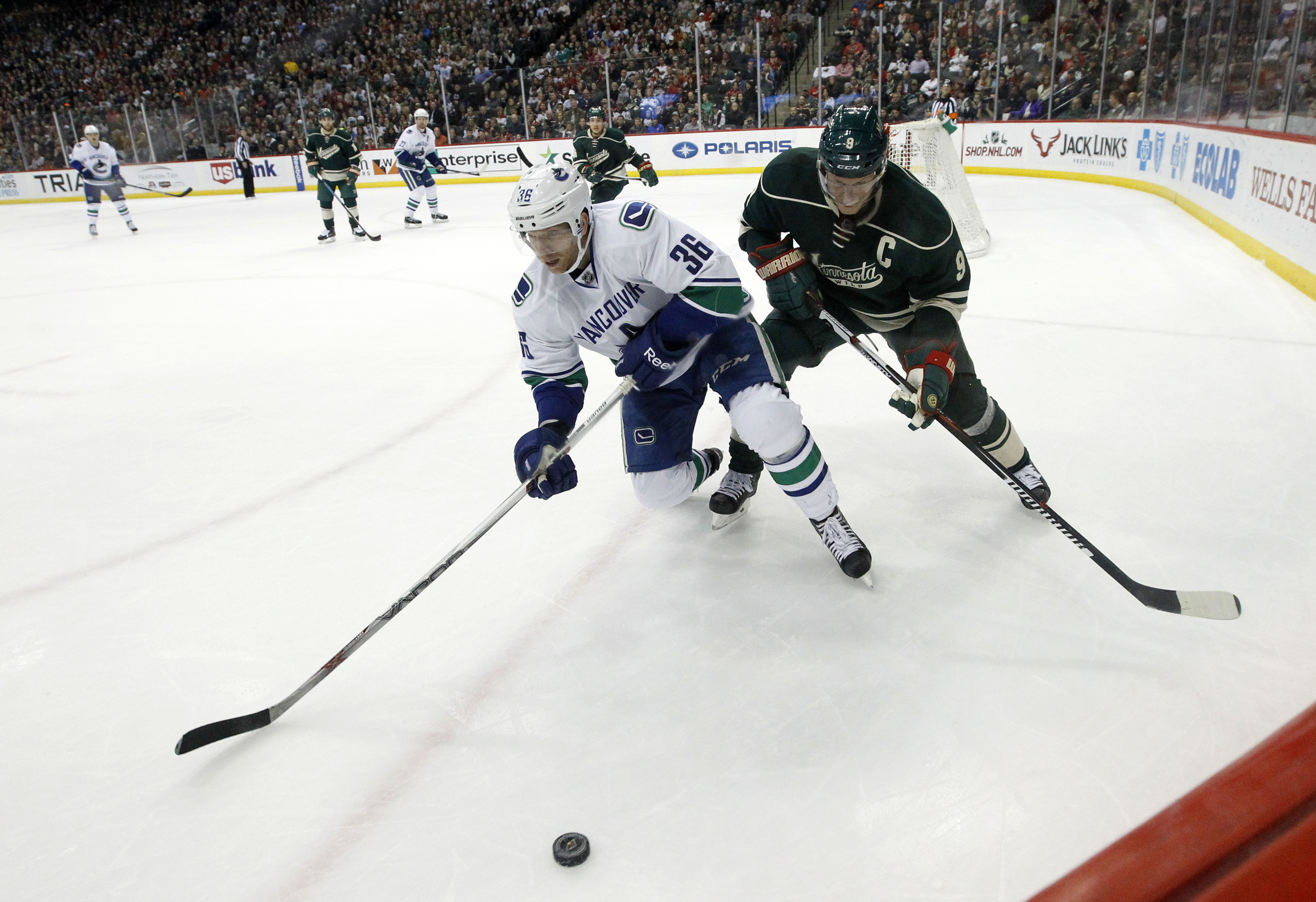 Vancouver Canucks right wing Jannik Hansen (36), of Denmark, and Minnesota Wild center Mikko Koivu (9), of Finland, chase the puck during the second period of an NHL hockey game in St. Paul, Minn., Wednesday, Nov. 25, 2015. (AP Photo/Ann Heisenfelt)