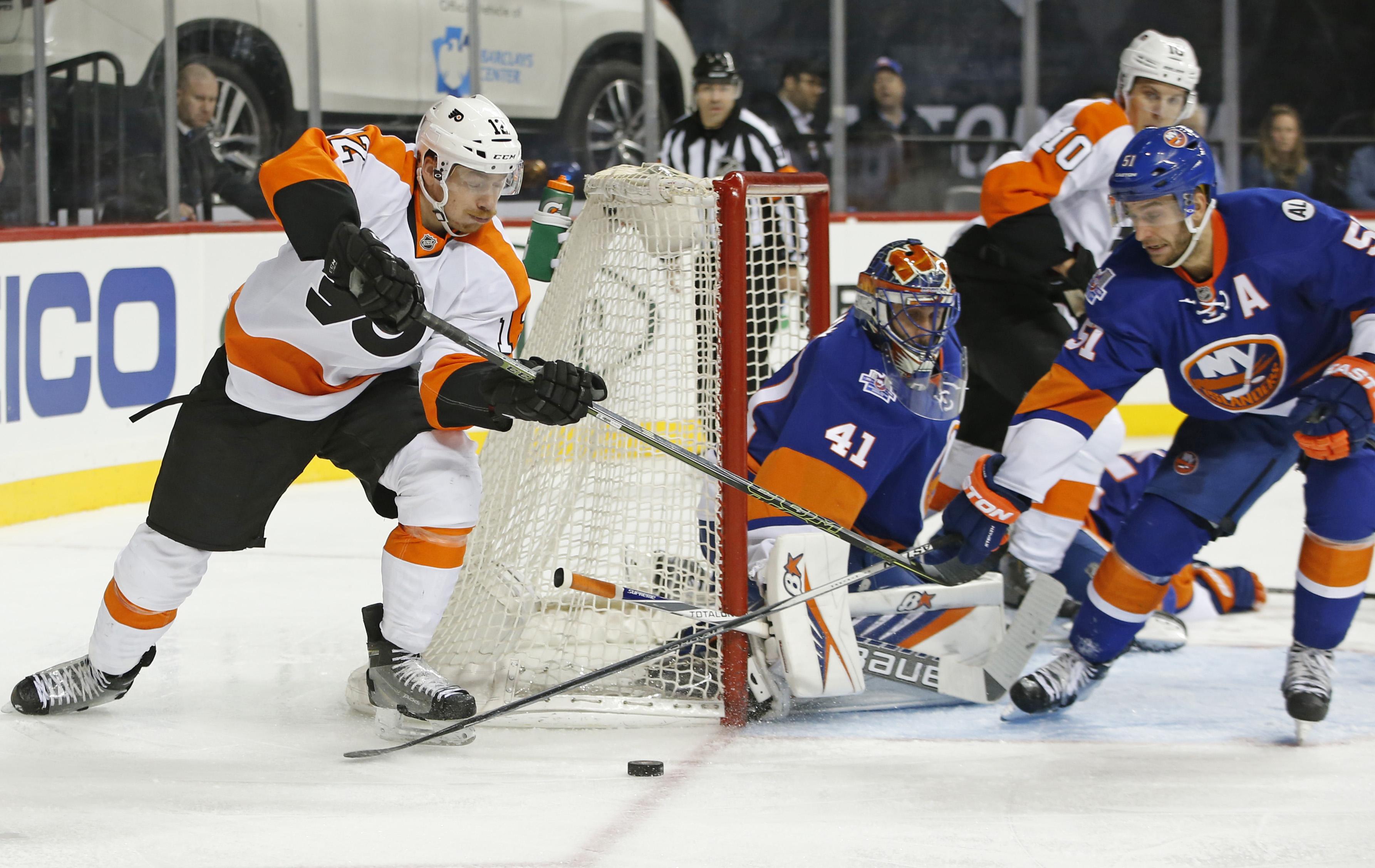 New York Islanders center Frans Nielsen (51) of Denmark defends Philadelphia Flyers left wing Michael Raffl (12) of Austria as New York Islanders goalie Jaroslav Halak (41) of Slovakia keeps his eye on the puck in the third period of an NHL hockey game in