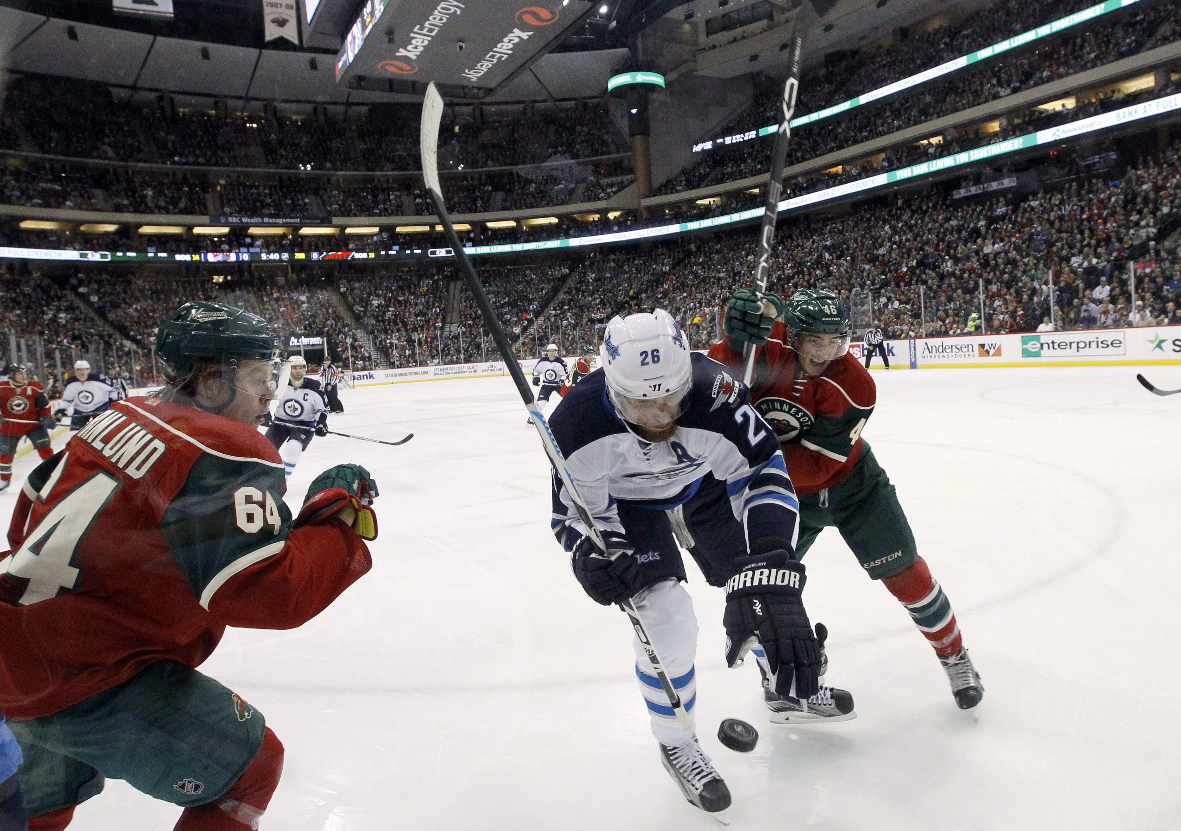 Winnipeg Jets right wing Blake Wheeler (26), Minnesota Wild defenseman Jared Spurgeon, right, and Wild center Mikael Granlund (64), of Finland, chase the puck during the second period of an NHL hockey game in St. Paul, Minn., Friday, Nov. 27, 2015. (AP Ph
