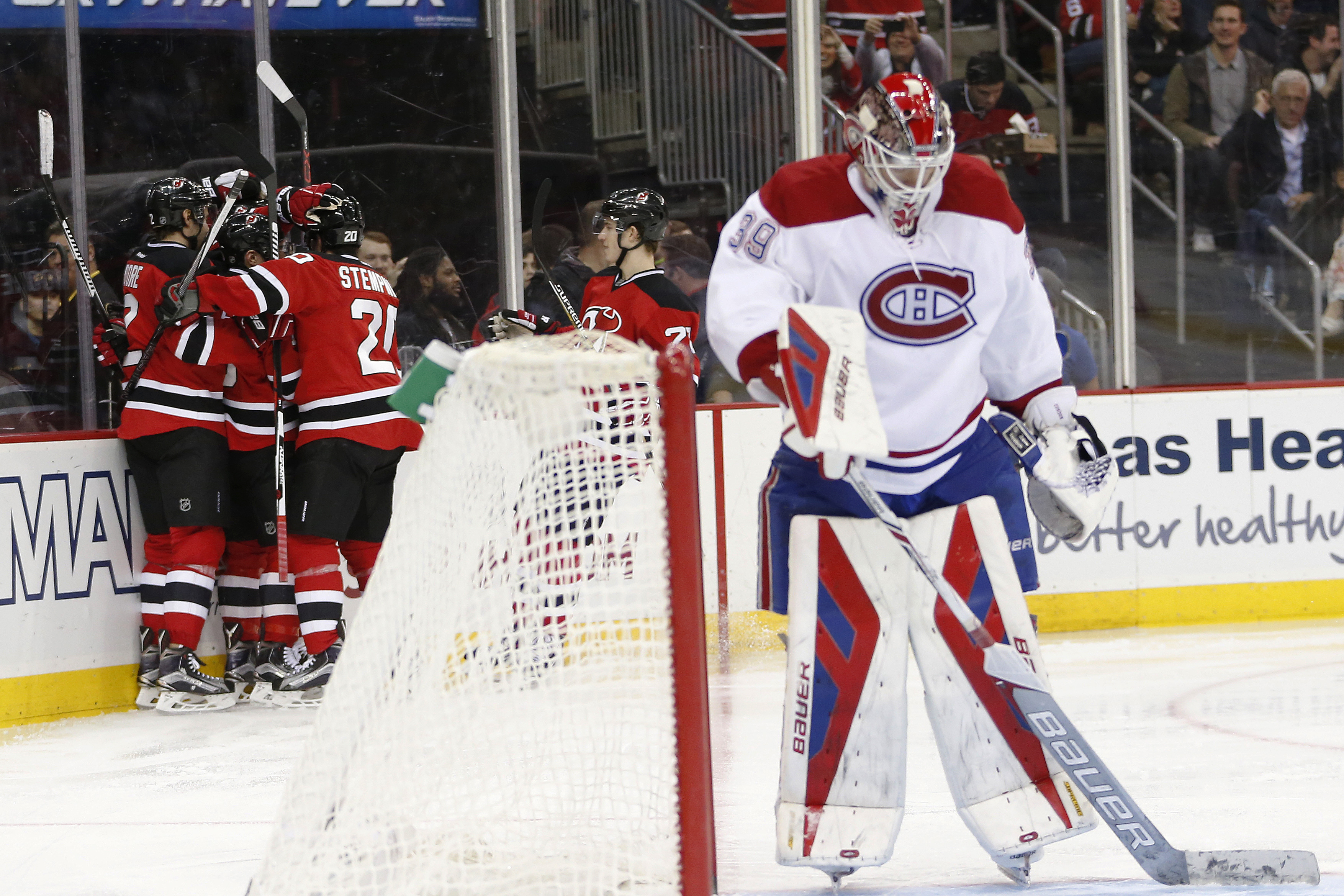 New Jersey Devils, left, celebrate after Adam Henrique scored a goal on Montreal Canadiens goalie Mike Condon, foreground, during the second period of an NHL hockey game, Friday, Nov. 27, 2015, in Newark, N.J. (AP Photo/Julio Cortez)
