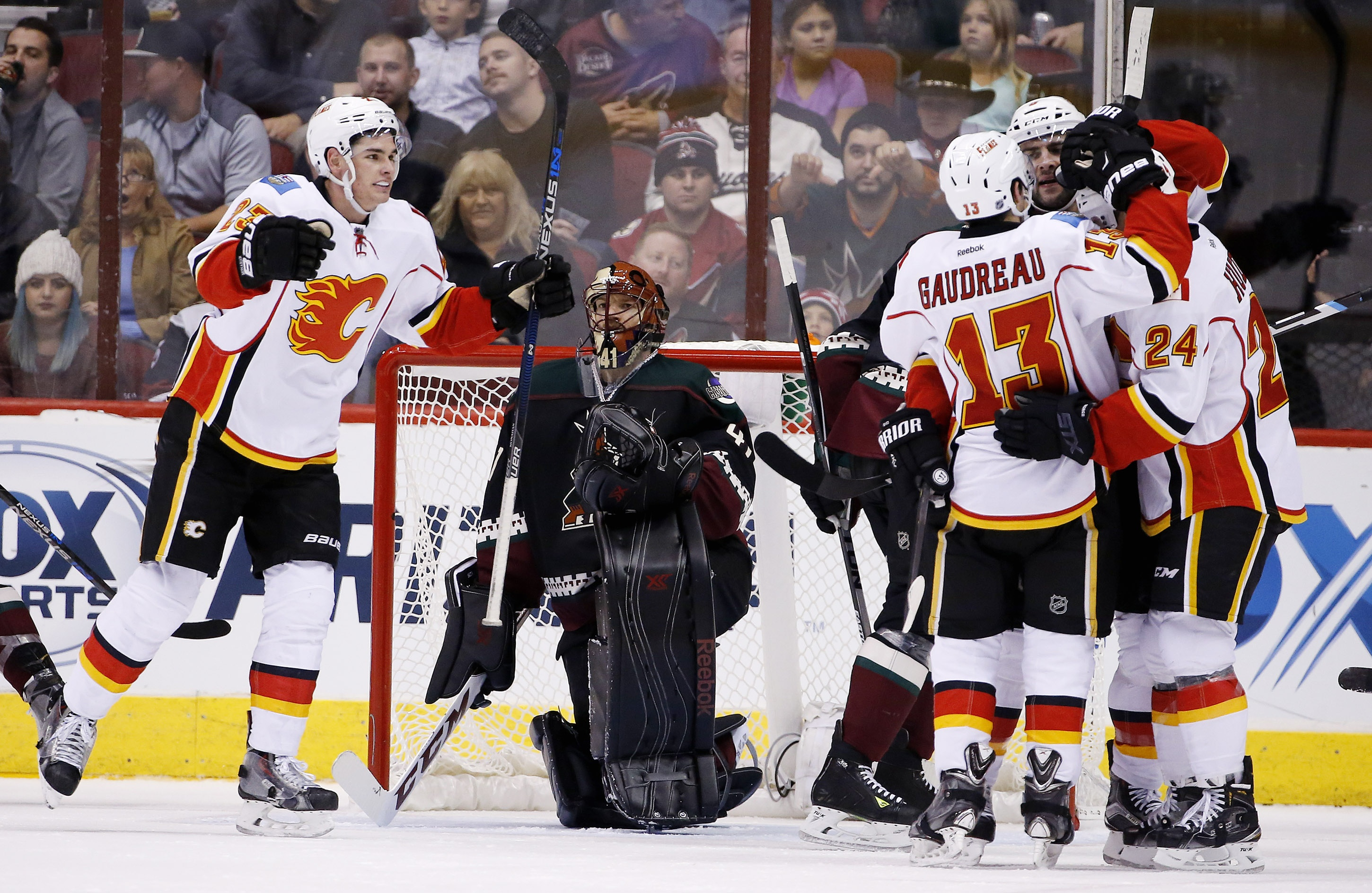 Calgary Flames' Mark Giordano celebrates his goal against Arizona Coyotes' Mike Smith, second from left, with teammates Johnny Gaudreau (13), Jiri Hudler (24), of the Czech Republic, and Sean Monahan, left, during the second period of an NHL hockey game F