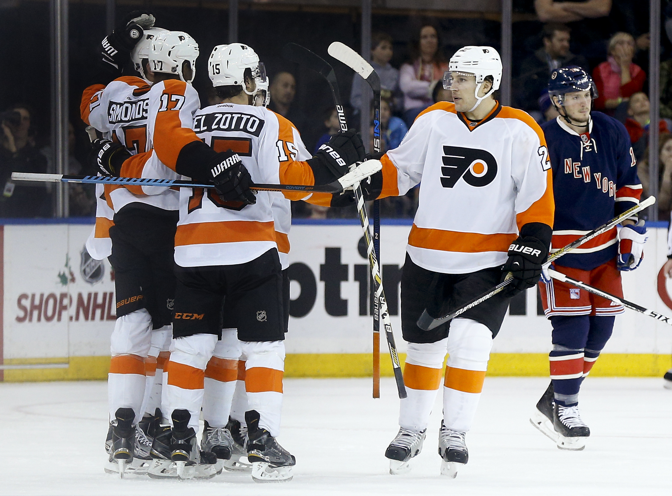 Philadelphia Flyers right wing Wayne Simmonds (17) celebrates with defenseman Michael Del Zotto (15) and defenseman Luke Schenn (22) after scoring a goal against the New York Rangers during the second period of an NHL hockey game, Saturday, Nov. 28, 2015,