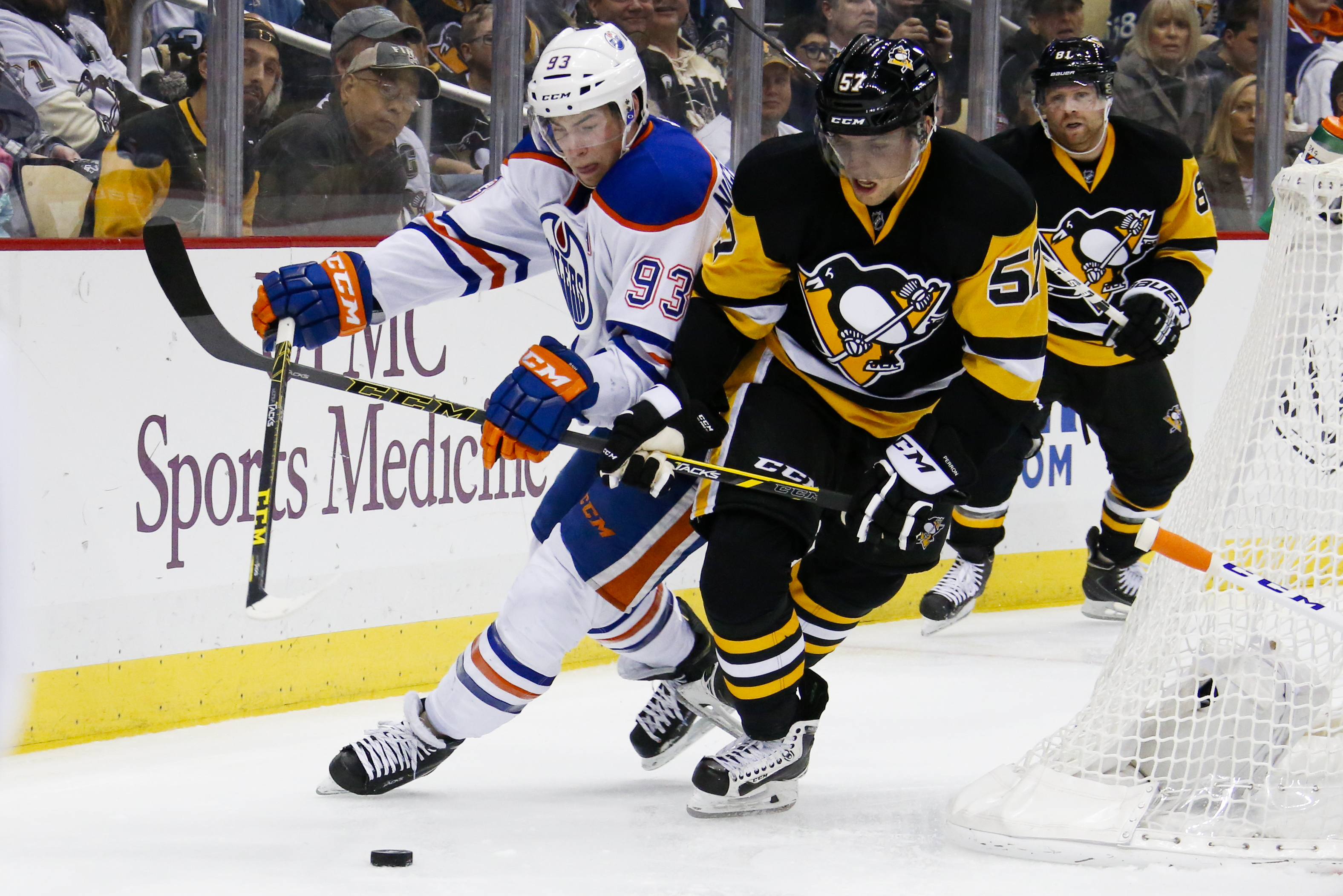 Pittsburgh Penguins' David Perron (57) and Edmonton Oilers' Ryan Nugent-Hopkins (93) battle for the puck during the second period of an NHL hockey game in Pittsburgh, Saturday, Nov. 28, 2015.(AP Photo/Gene J. Puskar)