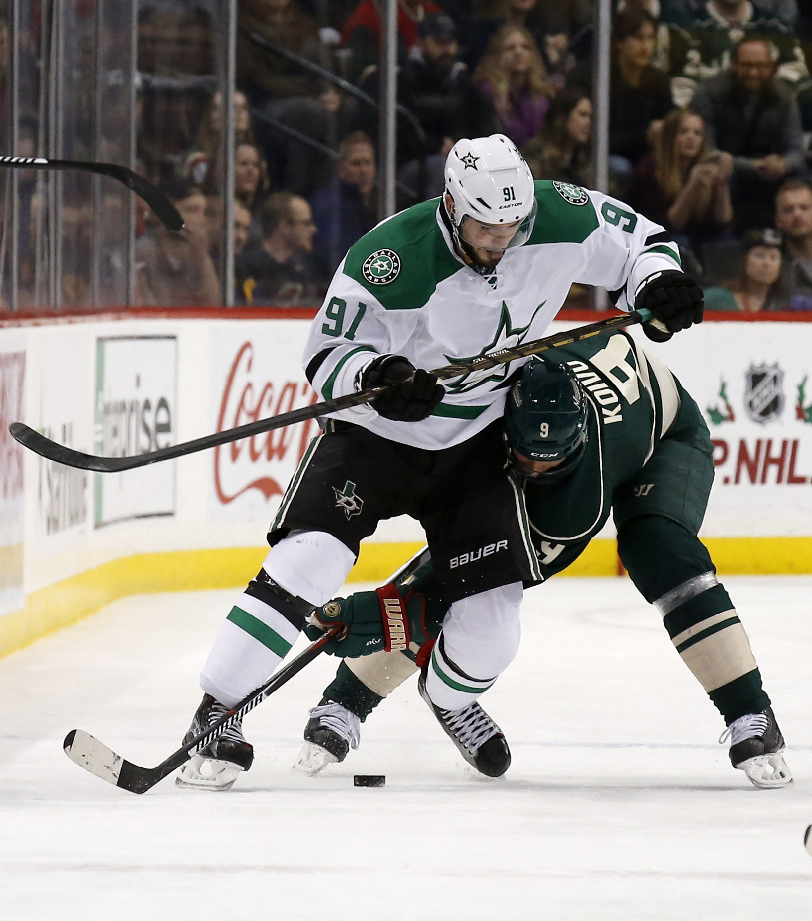 Dallas Stars center Tyler Seguin (91) and Minnesota Wild center Mikko Koivu (9), of Finland, battle for the puck during the second period of an NHL hockey game in St. Paul, Minn., Saturday, Nov. 28, 2015. (AP Photo/Ann Heisenfelt)