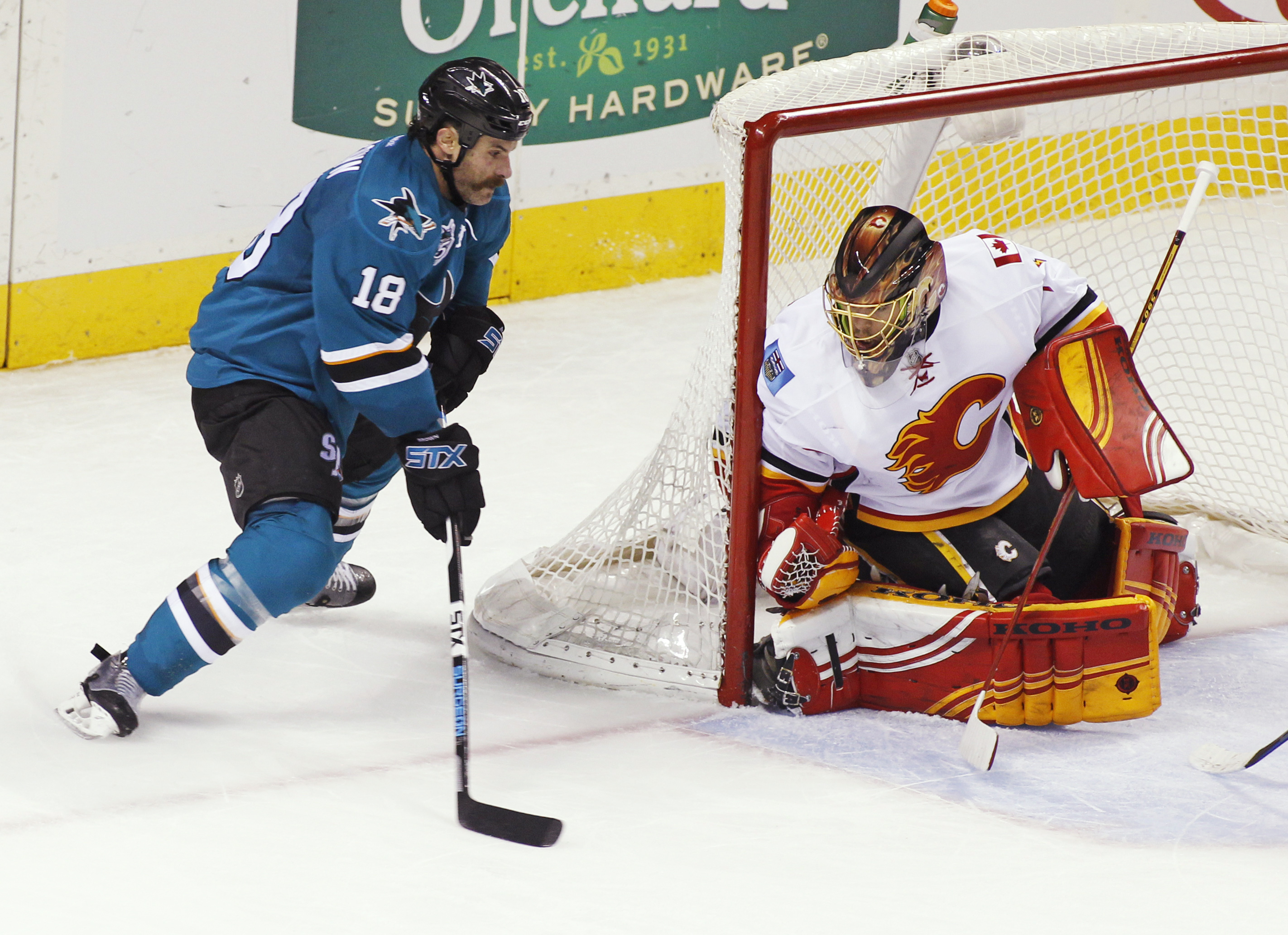 San Jose Sharks' Mike Brown, left, shoots as Calgary Flames goalie Jonas Hiller defends during the second period of an NHL hockey game Saturday, Nov. 28, 2015, in San Jose, Calif. (AP Photo/George Nikitin)