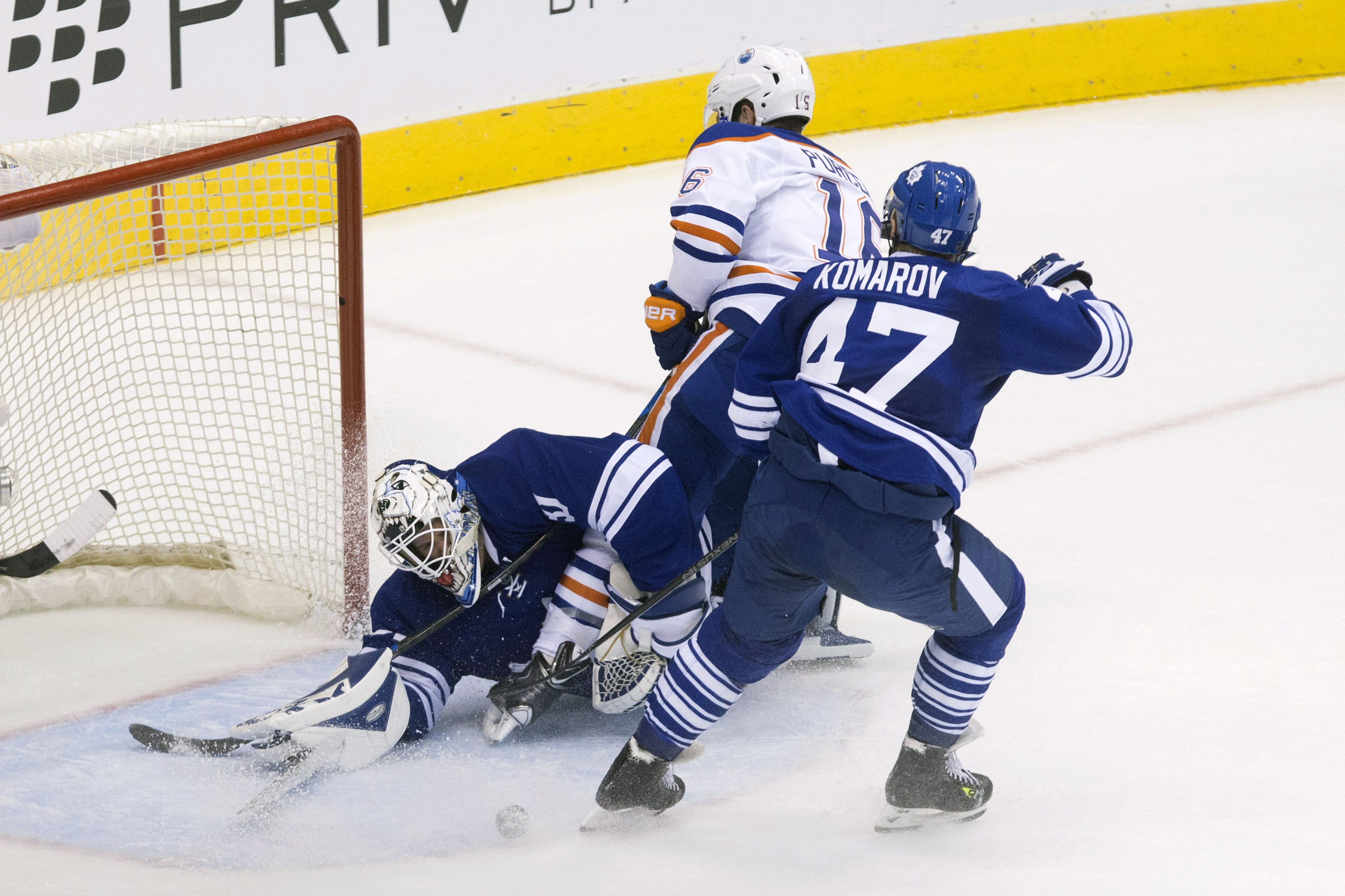 Toronto Maple Leafs goaltender Garret Sparks reaches to clear the puck after making a save from Edmonton Oilers' Teddy Purcell, center, as Maple Leafs' Leo Komarov defends during the second period of an NHL hockey game in Toronto on Monday, Nov. 30, 2015.