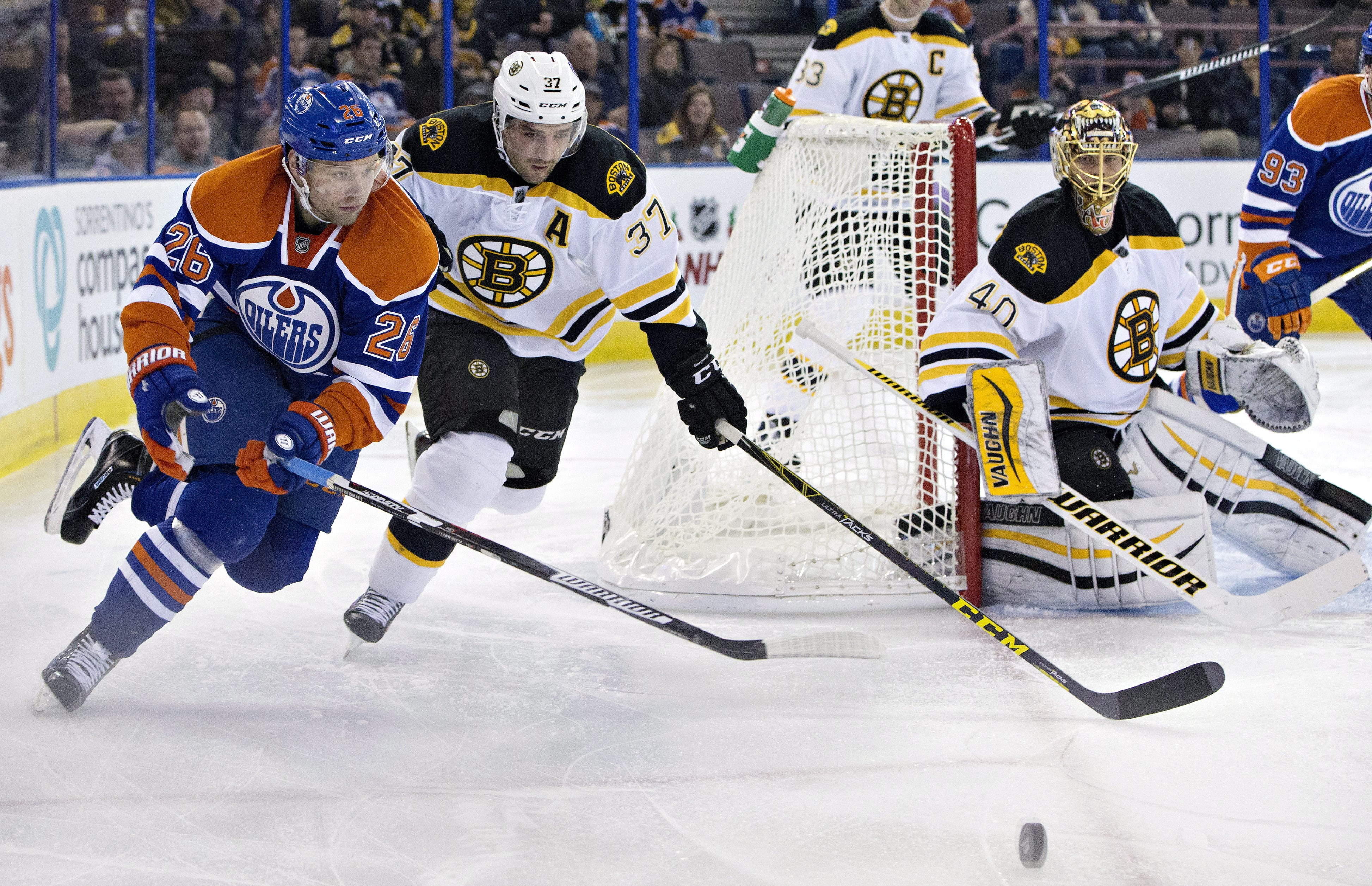 Boston Bruins' Patrice Bergeron (37) and Edmonton Oilers' Iiro Pakarinen (26) chase the rebound from goalie Tuukka Rask (40) during the second period of an NHL hockey game, Wednesday, Dec. 2, 2015, in Edmonton, Alberta. (Jason Franson/The Canadian Press v