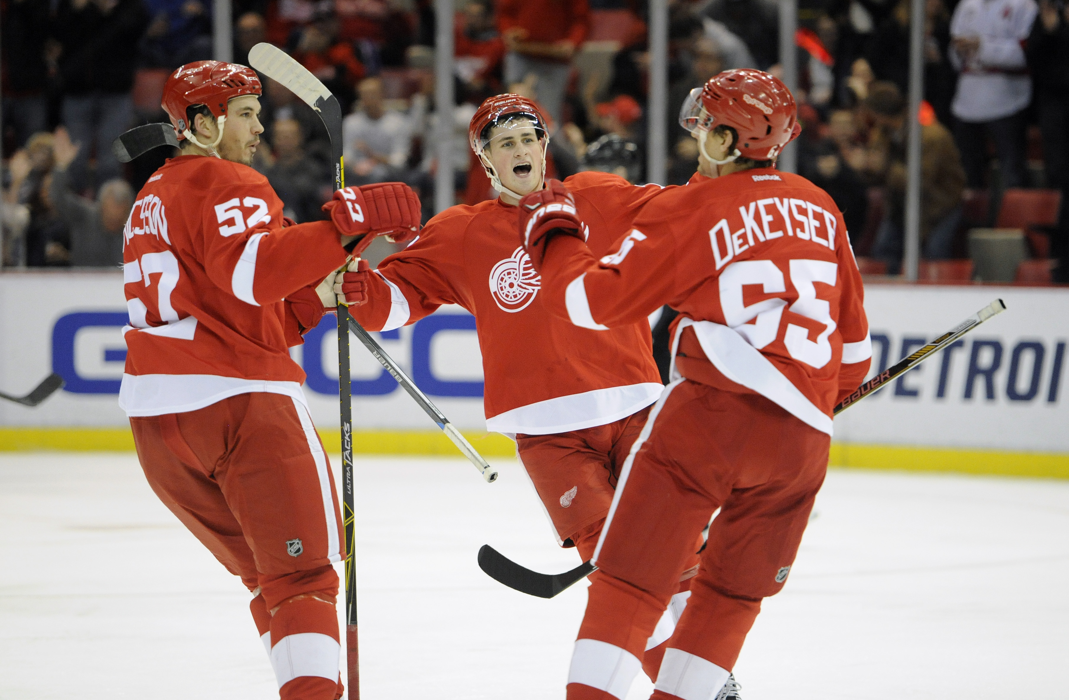 Detroit Red Wings defenseman Jonathan Ericsson (52) of Sweden, and center Dylan Larkin (71), middle, congratulate defenseman Danny DeKeyser (65) after DeKeyser scores against the Arizona Coyotes during the second period of an NHL hockey game in Detroit, T