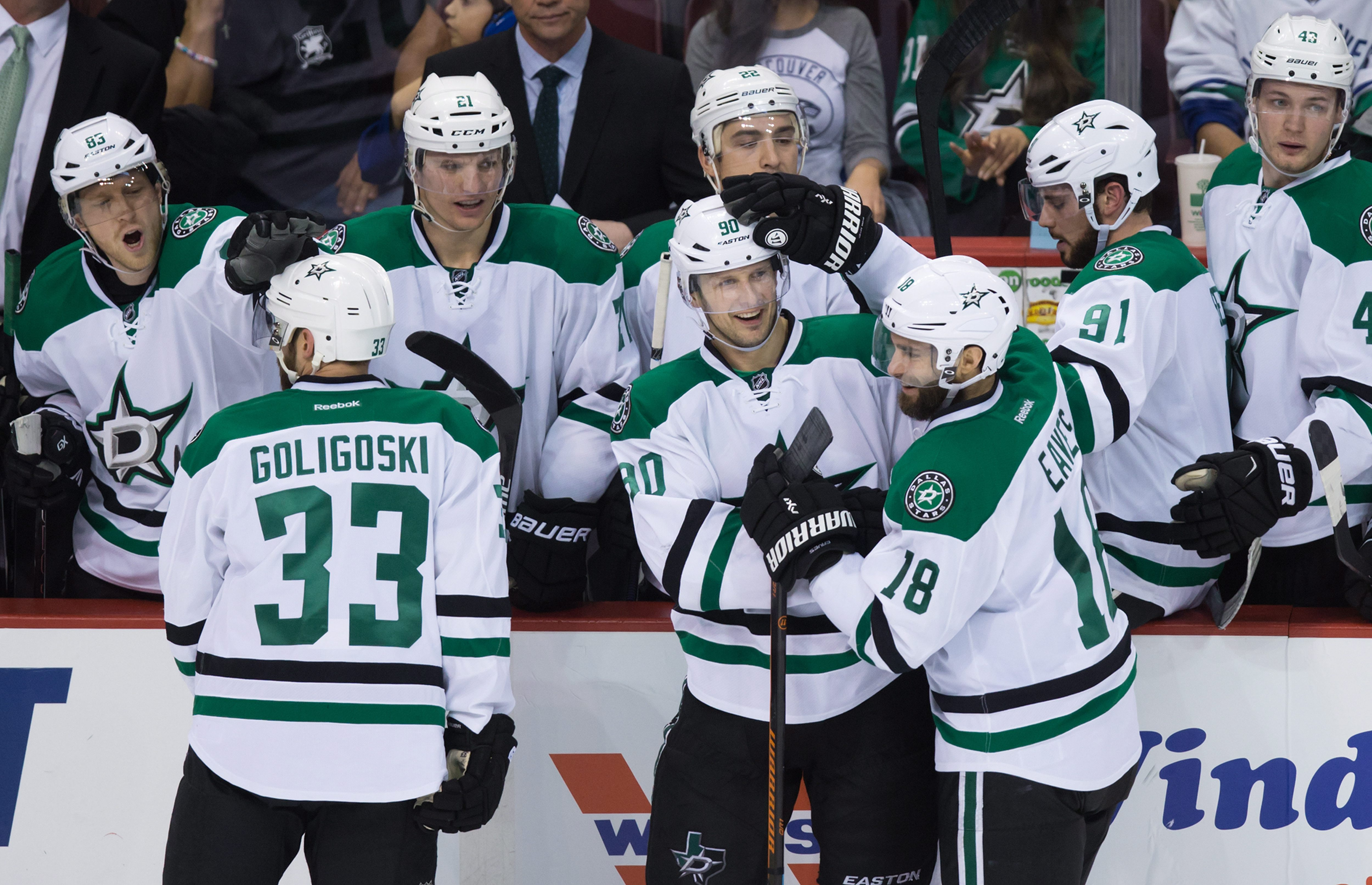 Dallas Stars' Jason Spezza, center, and Patrick Eaves, front right, celebrate Spezza's empty-net goal against the Vancouver Canucks during the third period of an NHL hockey game Thursday, Dec. 3, 2015, in Vancouver, British Columbia. (Darryl Dyck/The Cana