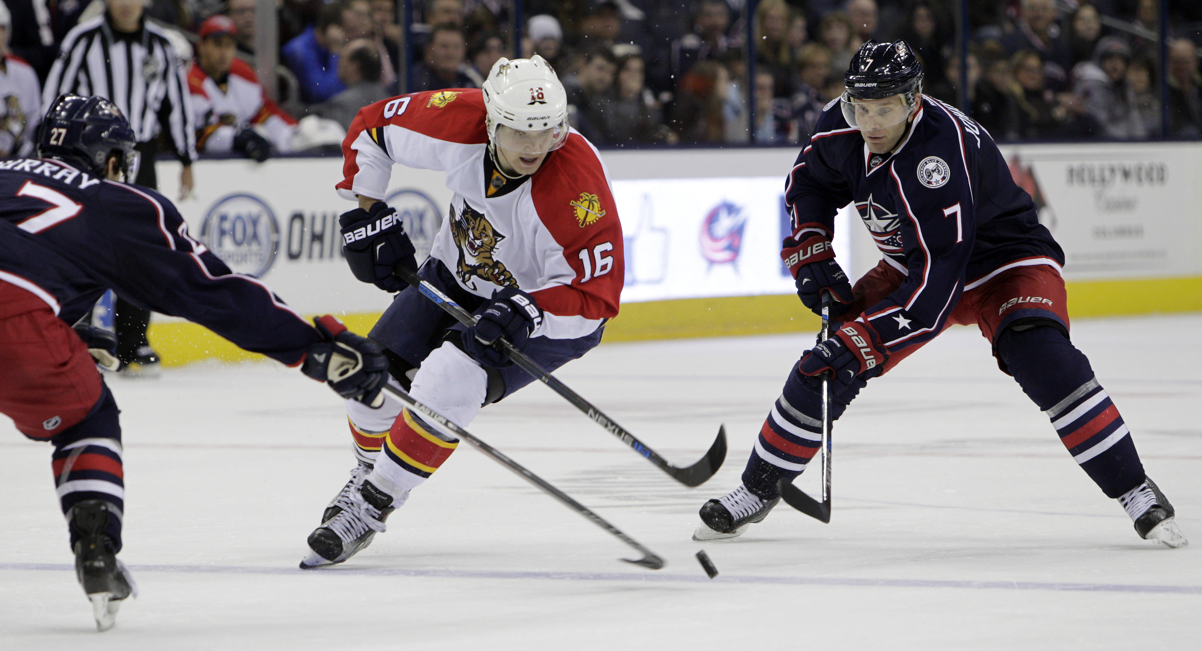 Florida Panthers' Aleksander Barkov, center, of Finland, carries the puck between Columbus Blue Jackets' Ryan Murray, left, and Jack Johnson during the third period of an NHL hockey game Friday, Dec. 4, 2015, in Columbus, Ohio. The Panthers won 2-1 in a s
