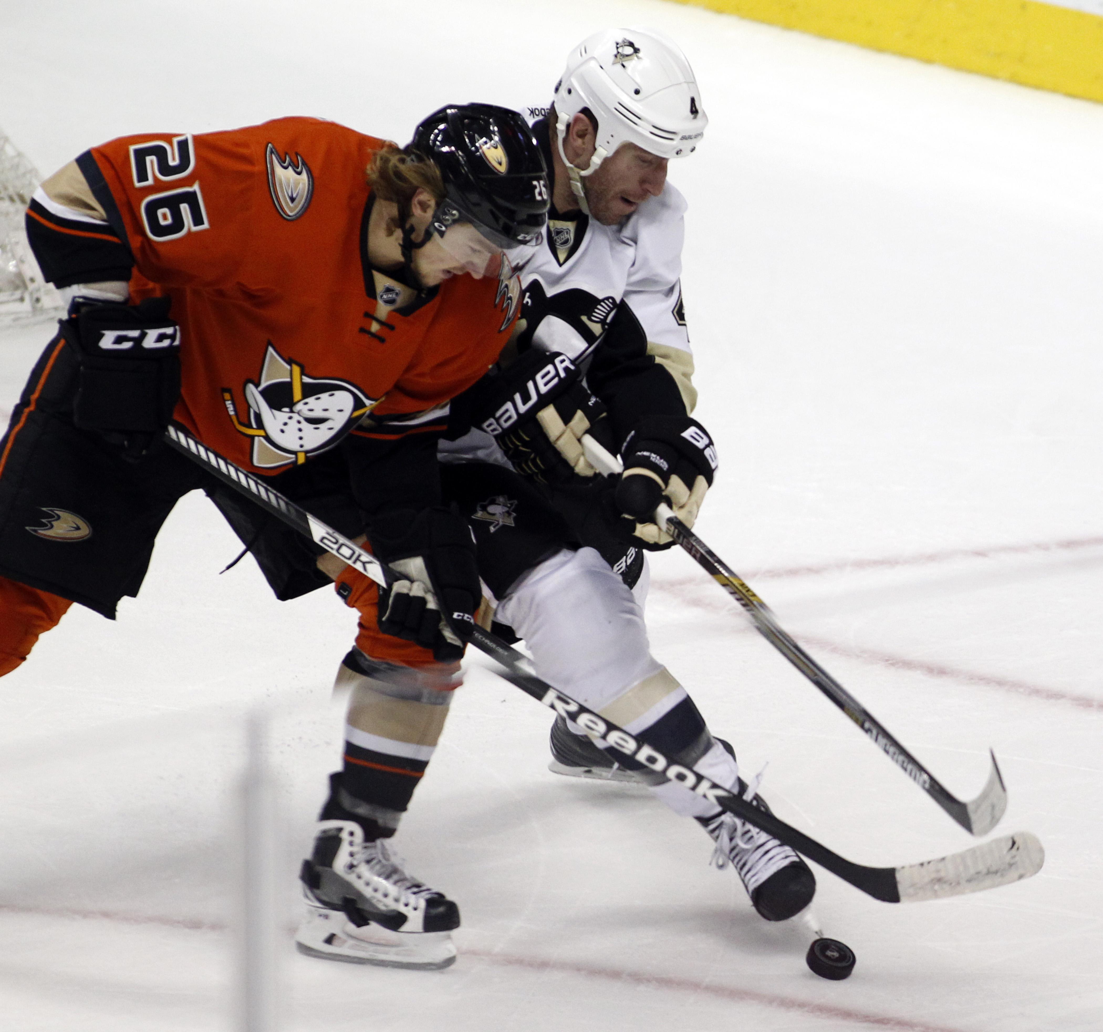 Anaheim Ducks left wing Carl Hagelin, left, battles Pittsburgh Penguins defenseman Rob Scuderi, right, for the puck during the third period of an NHL hockey game in Anaheim, Calif., Sunday, Dec. 6, 2015.  The Ducks won 2-1. (AP Photo/Alex Gallardo)
