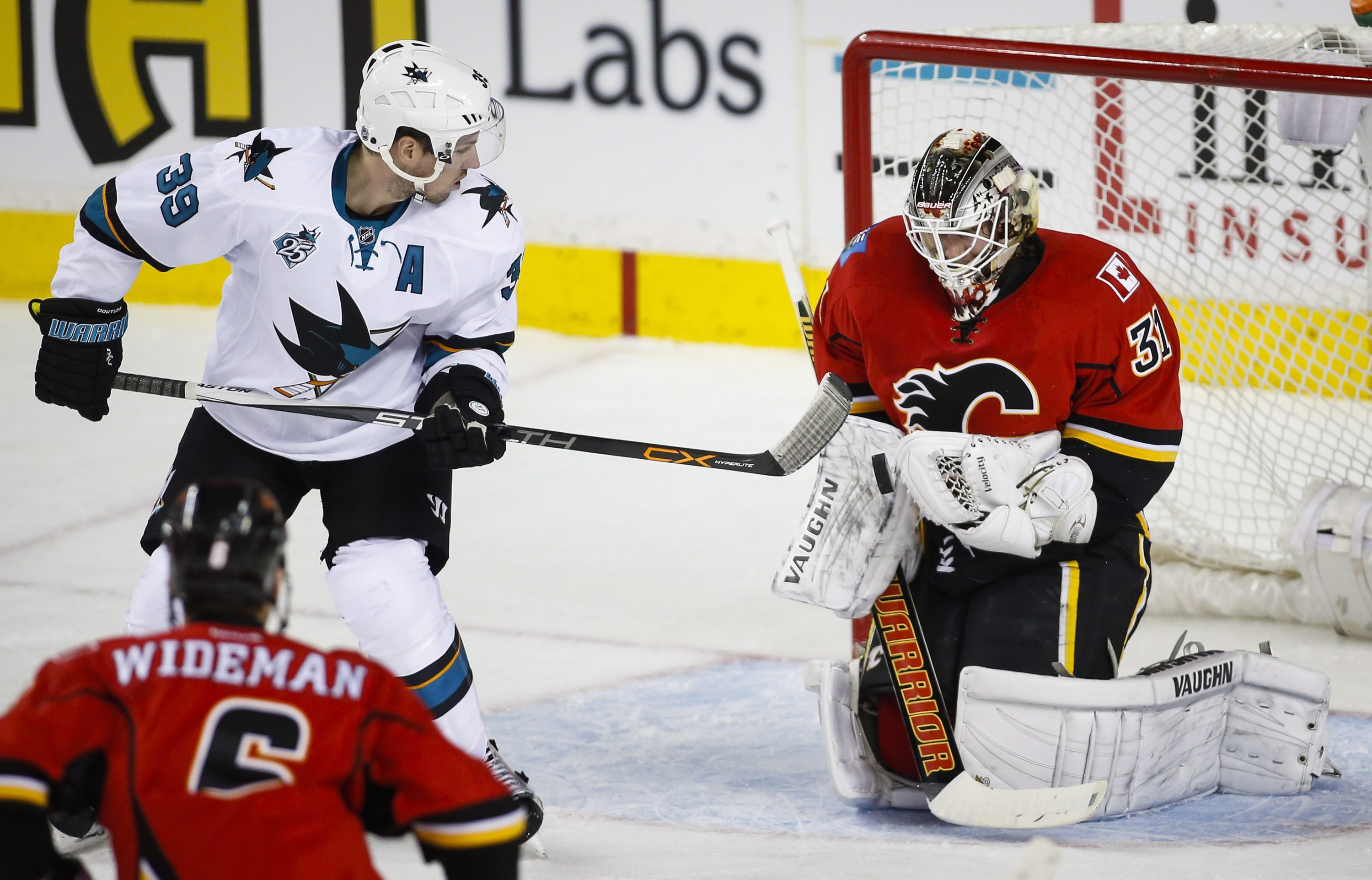 San Jose Sharks' Logan Couture, left, tries to get the puck past Calgary Flames' goalie Karri Ramo, of Finland, during first period NHL hockey action, in Calgary, on Tuesday, Dec. 8, 2015. (Jeff McIntosh/The Canadian Press via AP)