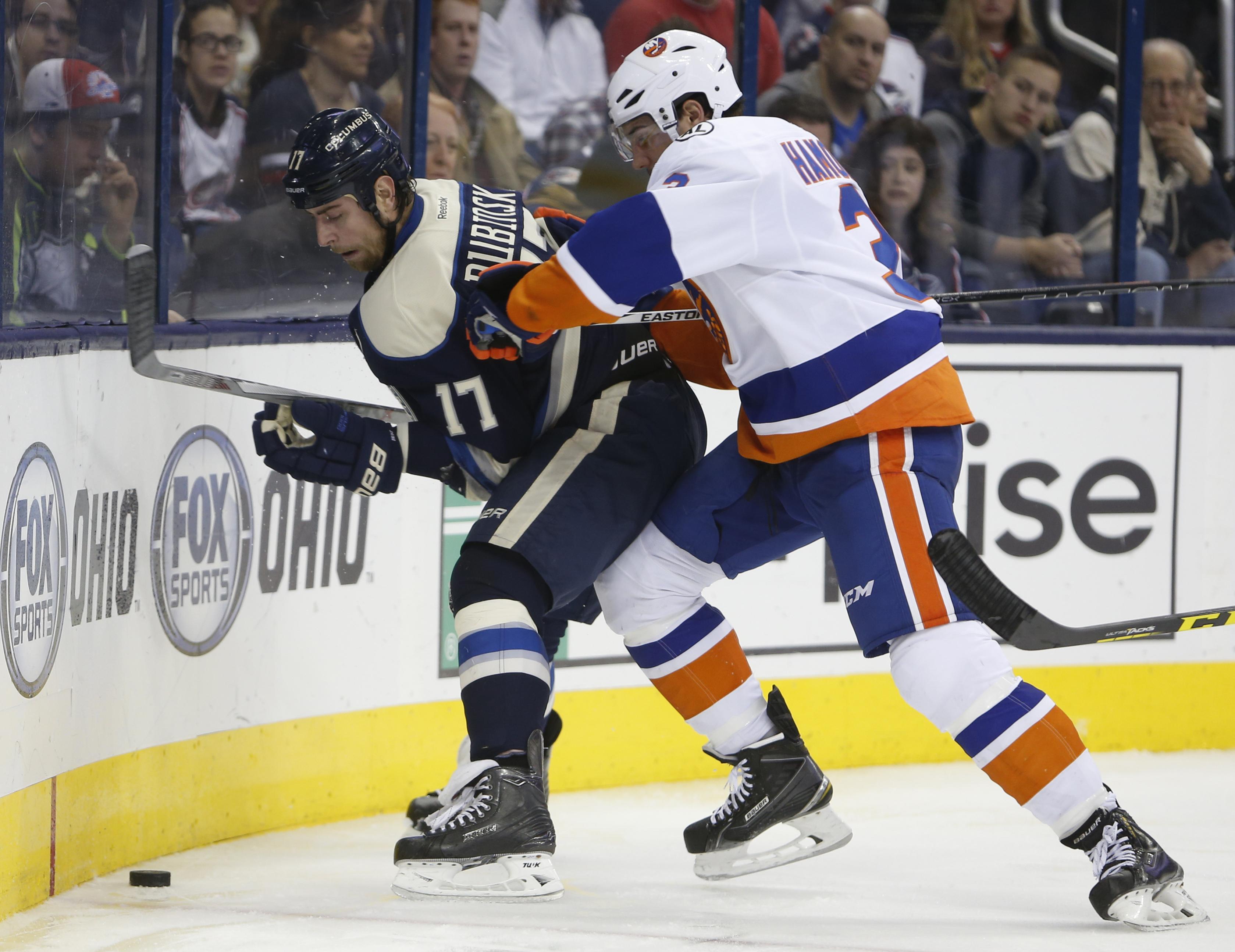 New York Islanders' Travis Hamonic, right, checks Columbus Blue Jackets' Brandon Dubinsky during the second period of an NHL hockey game Saturday, Dec. 12, 2015, in Columbus, Ohio. The Islanders beat the Blue Jackets 3-2 in overtime. (AP Photo/Jay LaPrete