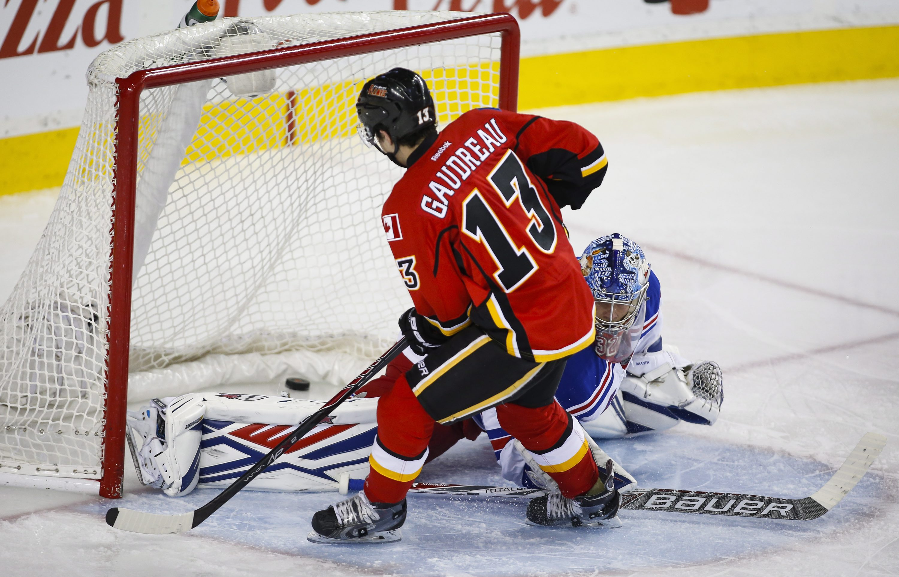 New York Rangers' goalie Antti Raanta, right, of Finland, lets in a goal from Calgary Flames' Johnny Gaudreau during third period NHL hockey action, in Calgary, on Saturday, Dec. 12, 2015. (Jeff McIntosh/The Canadian Press via AP)