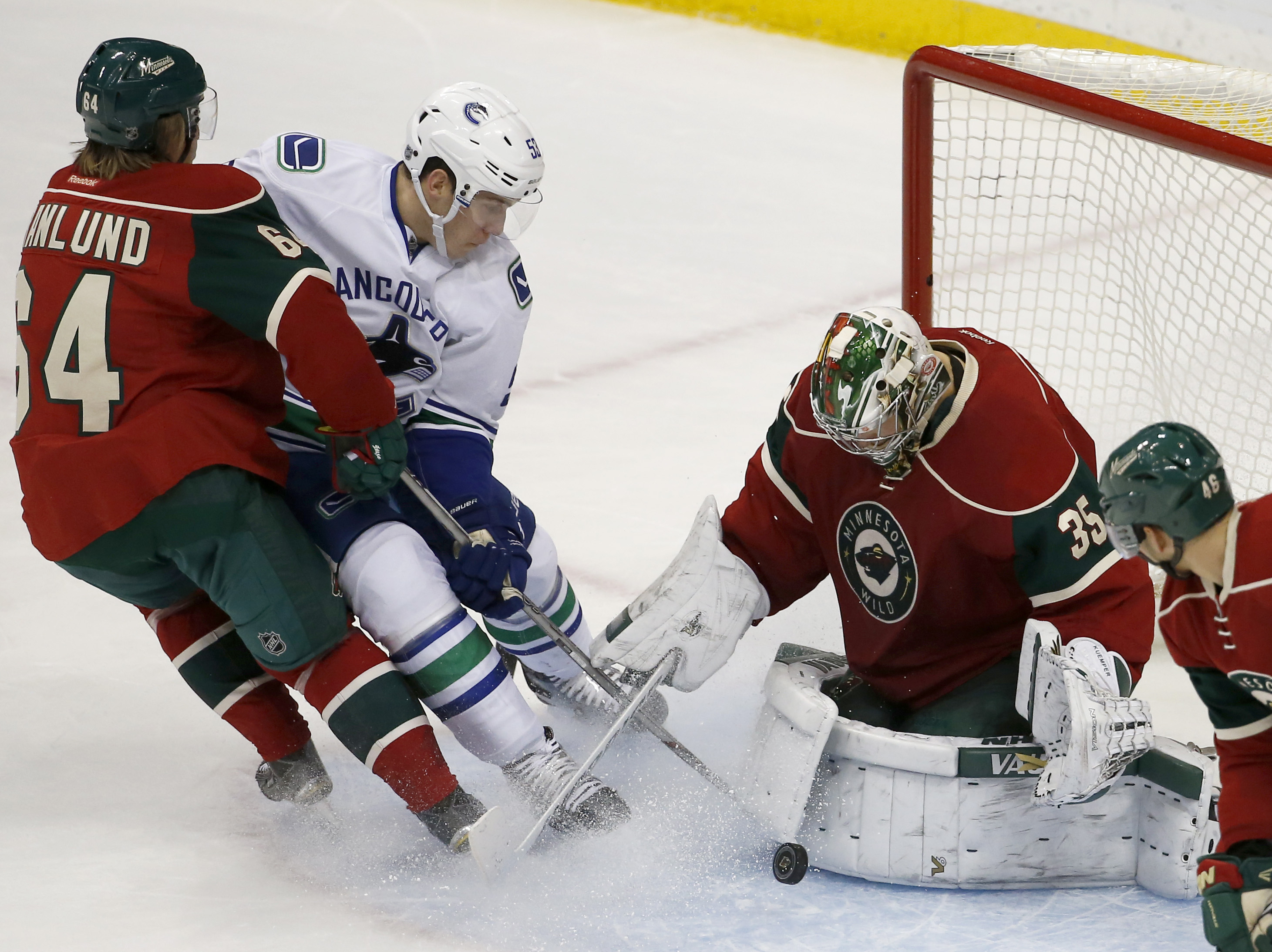 Minnesota Wild goalie Darcy Kuemper, right,  stops a shot by Vancouver Canucks center Bo Horvat, center, as Wild center Mikael Granlund (64), of Finland, tries to keep Horvat off the puck during the first period of an NHL hockey game in St. Paul, Minn., T