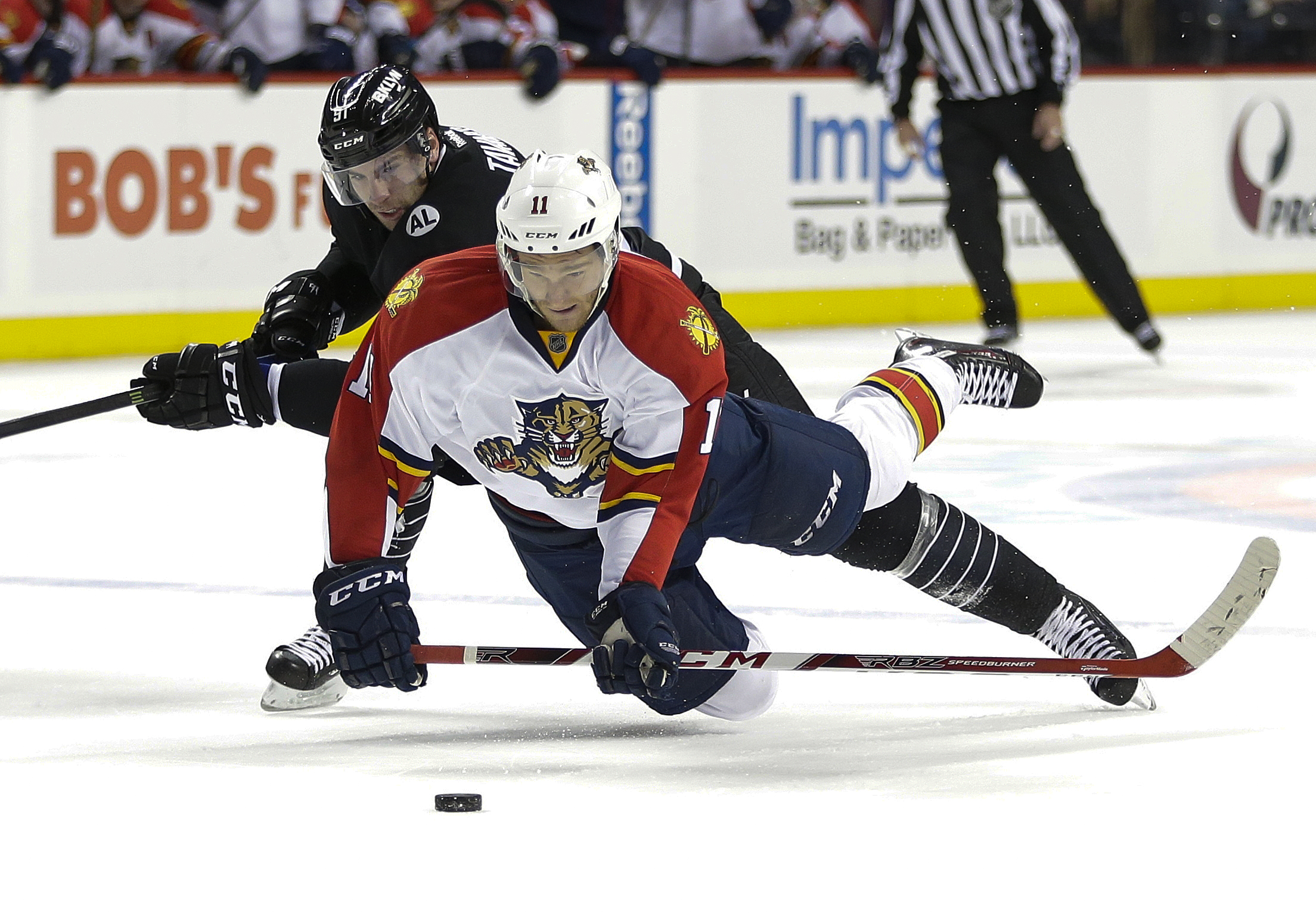Florida Panthers' Jonathan Huberdeau (11) shoots the puck toward an empty net as New York Islanders' John Tavares (91) knocks him down during the third period of an NHL hockey game Tuesday, Dec. 15, 2015, in New York. Huberdeau was awarded the goal on the