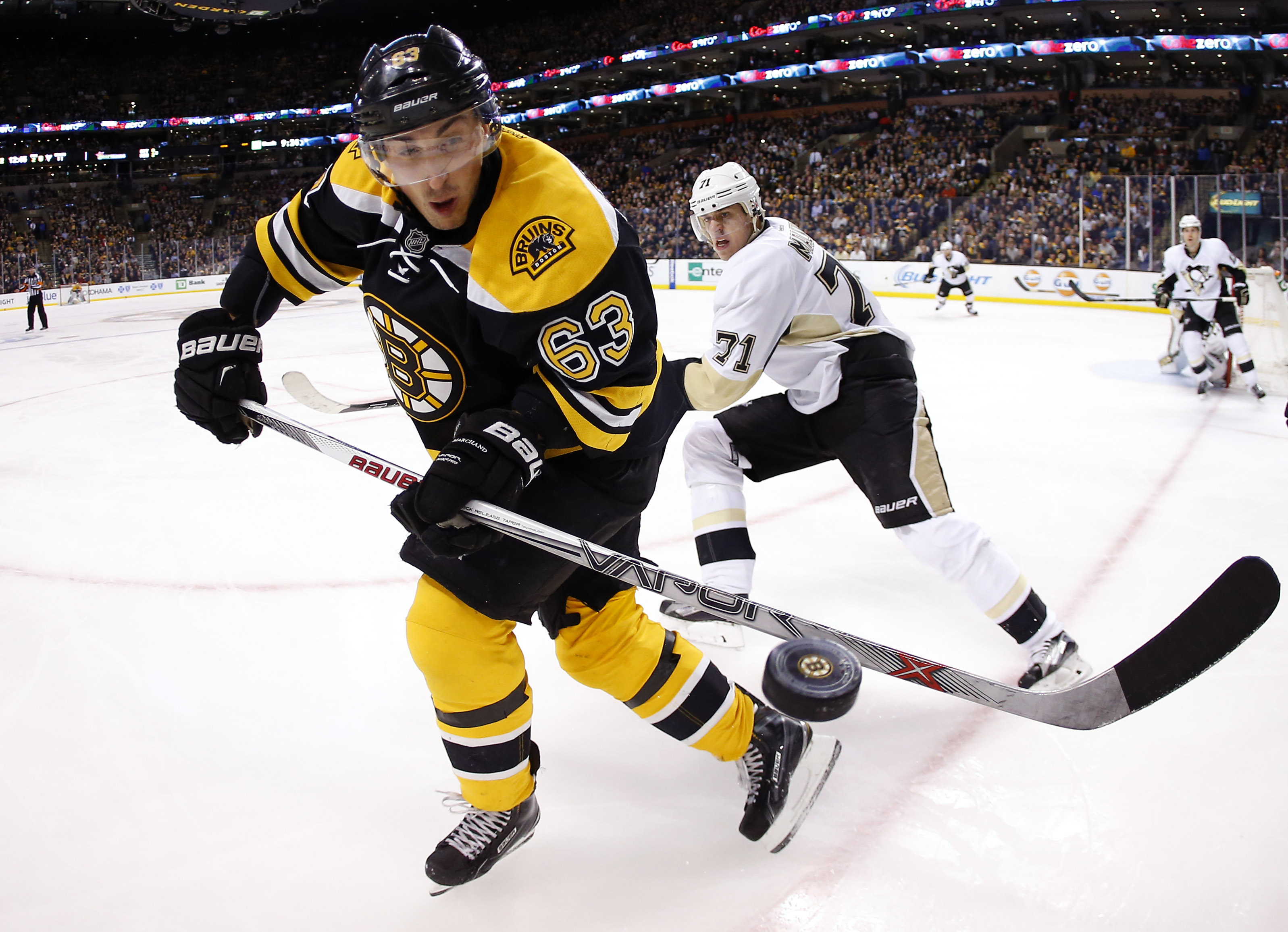 Boston Bruins' Brad Marchand eyes a loose puck in front of Pittsburgh Penguins' Evgeni Malkin during the third period of the Boston Bruins 3-0 win over the Pittsburgh Penguins in an NHL hockey game in Boston Wednesday, Dec. 16, 2015. (AP Photo/Winslow Tow